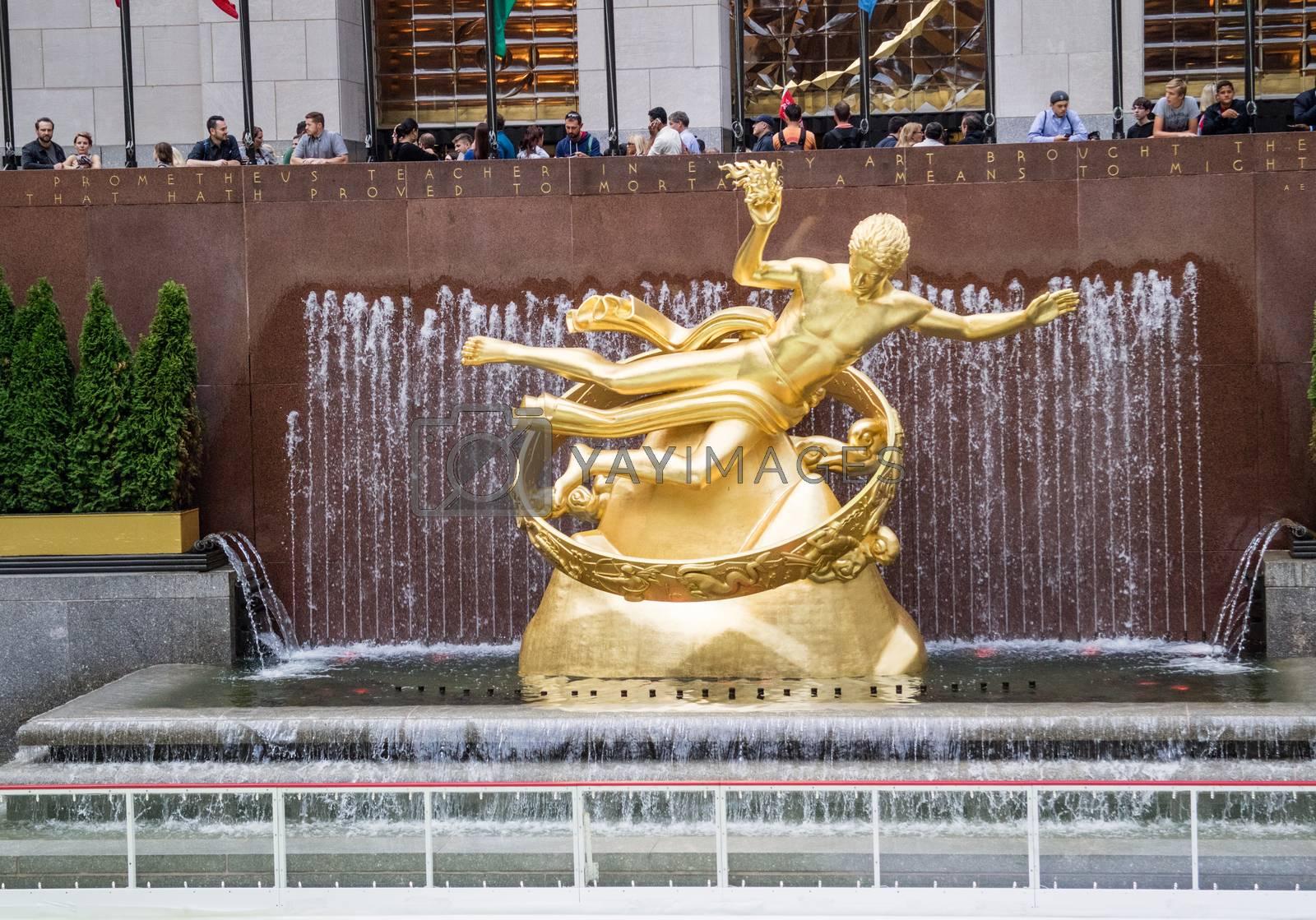 NEW YORK, USA, October 9, 2015: Unidentified people observing the Golden Prometheus statue at the Rockfeller Center Manhattan, New York.