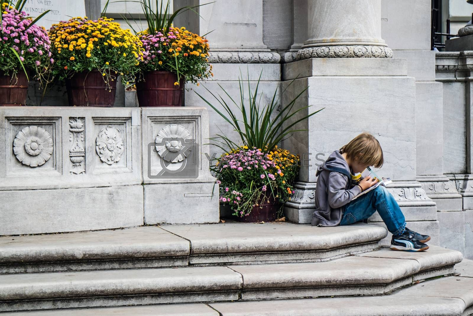 NEW YORK, USA, October 09, 2015: An unidentified boy reading a book at Bryant Park in Manhattan, New York City.
