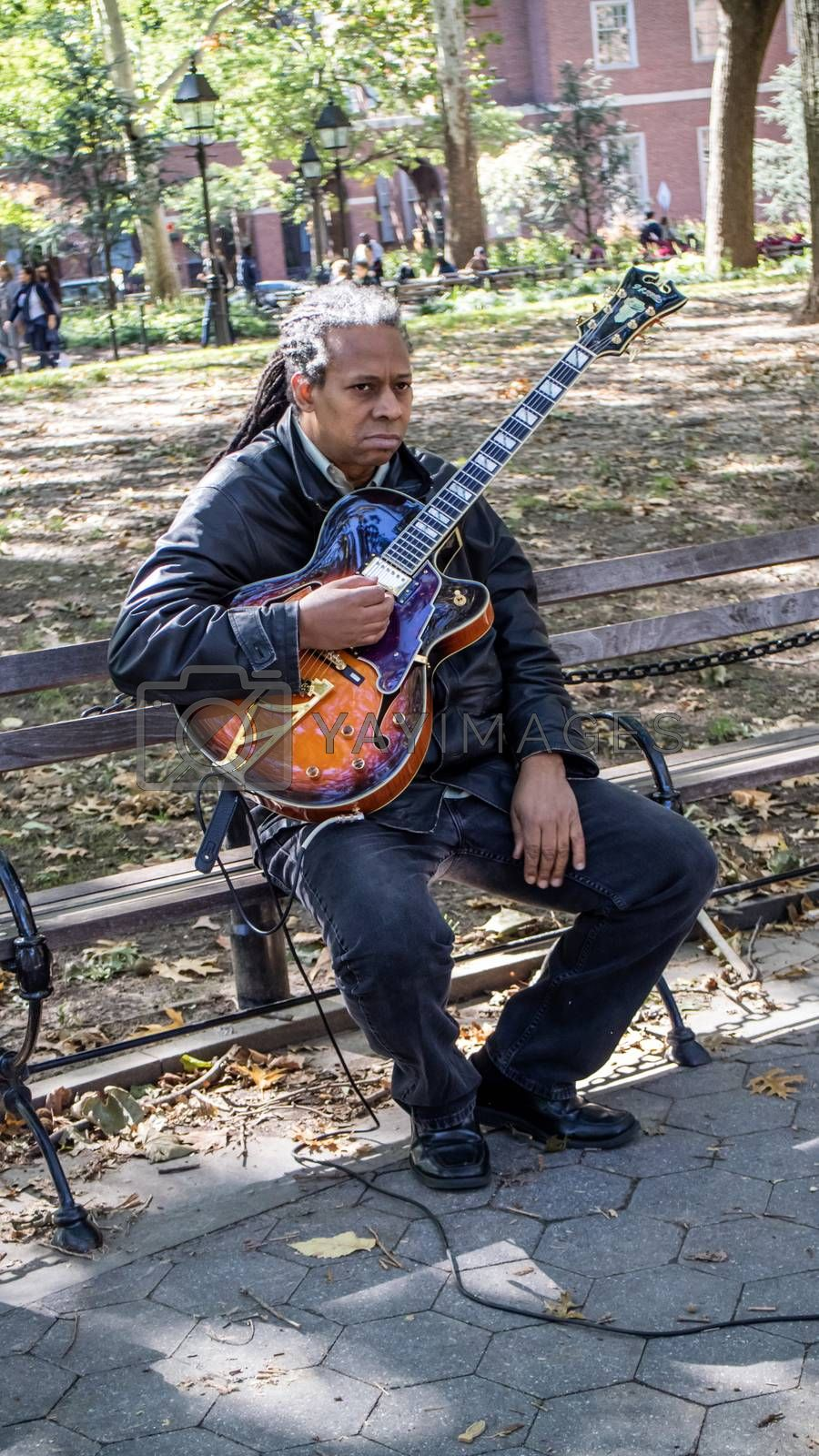 NEW YORK, USA, October 10, 2015: An unidentified lonely guitar player perform his songs in Washington Square Garden in Manhattan, New York.