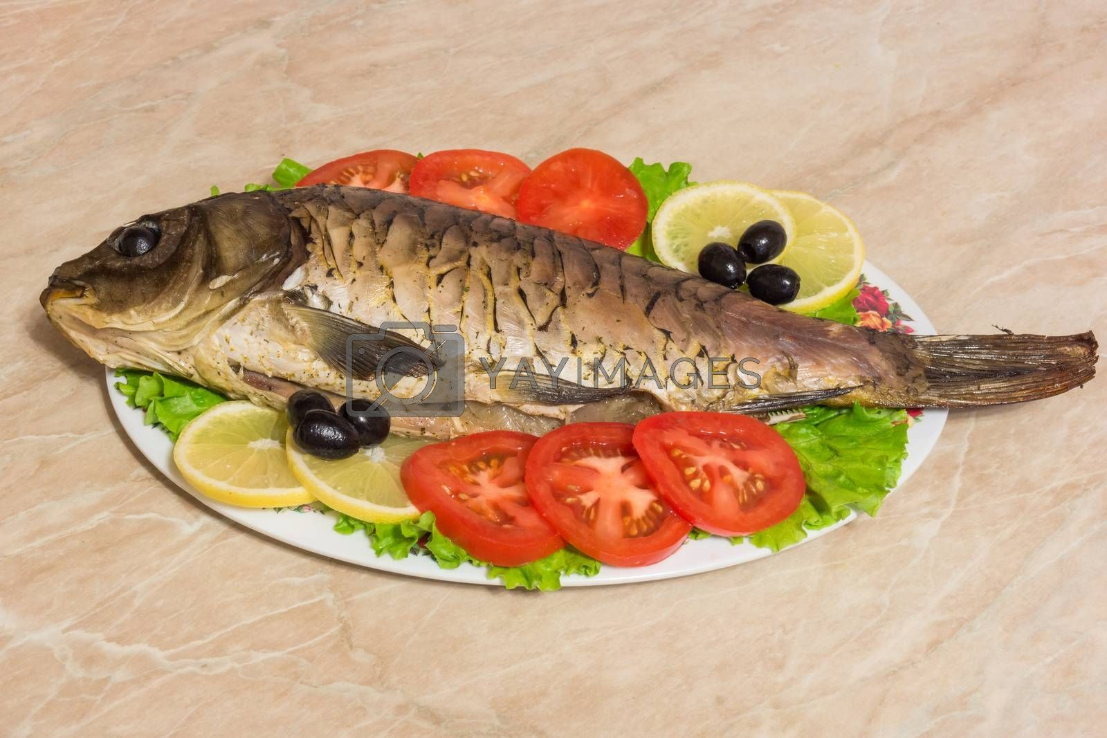 The photo shows a fish on a plate with tomatoes and olives.