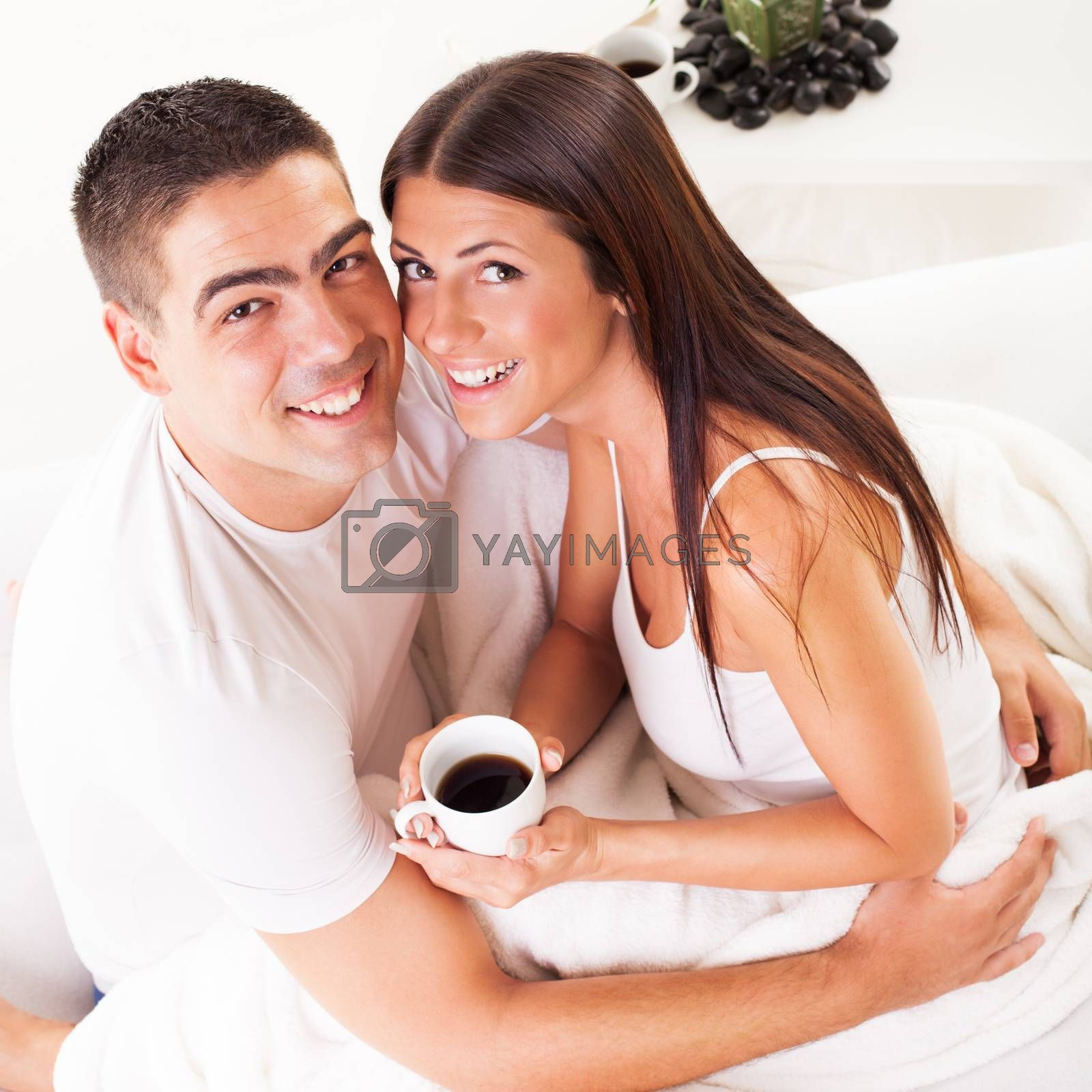 Young romantic couple in love sitting on the bed and drink coffee in the morning.