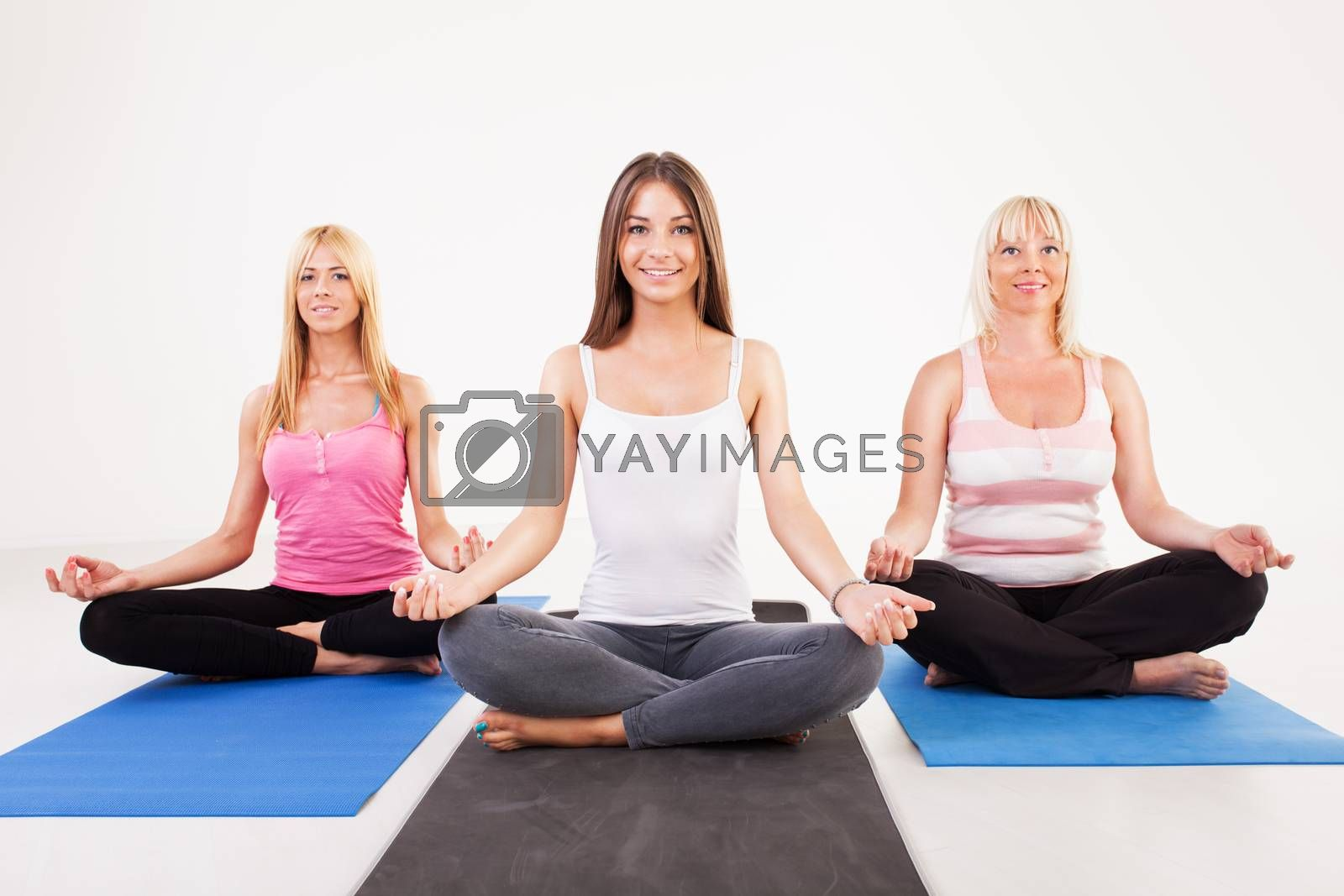 Three beautiful women sitting in lotus position.