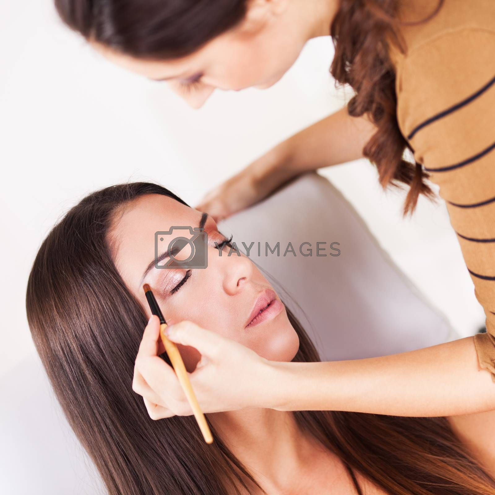 Female makeup artist darkening eyes with eye shadow on Young Attractive woman.