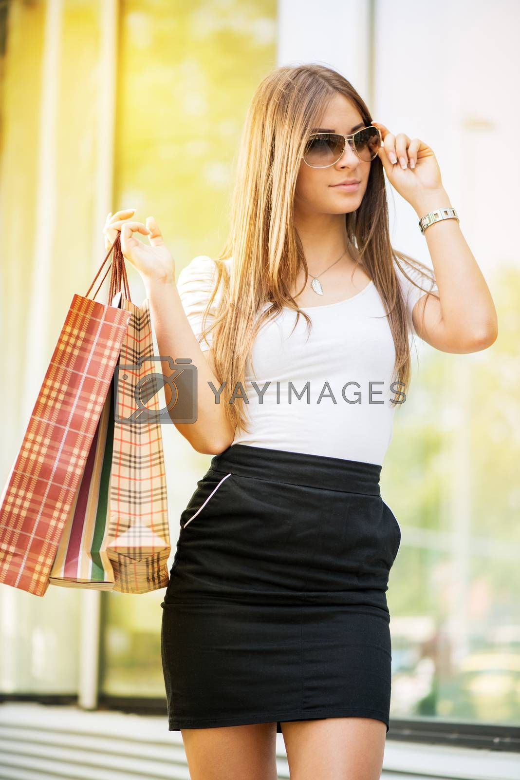 Beautiful young woman with the shopping bags walking in front of a shopping mall.