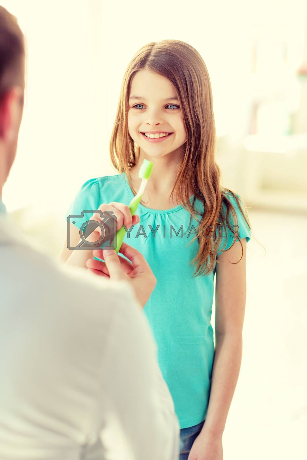 healthcare, child and medicine concept - male doctor giving toothbrush to smiling little girl