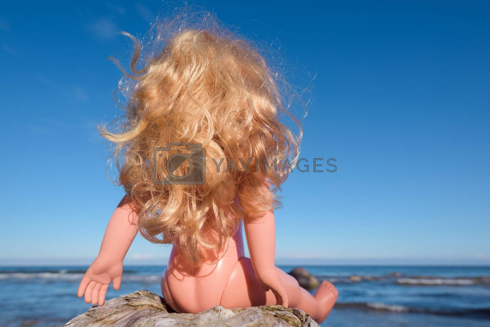Plastic Baby Doll with blonde long hair sitting on the seashore