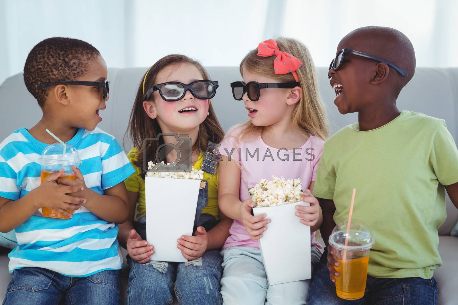 Happy kids enjoying popcorn and drinks while sitting on the couch
