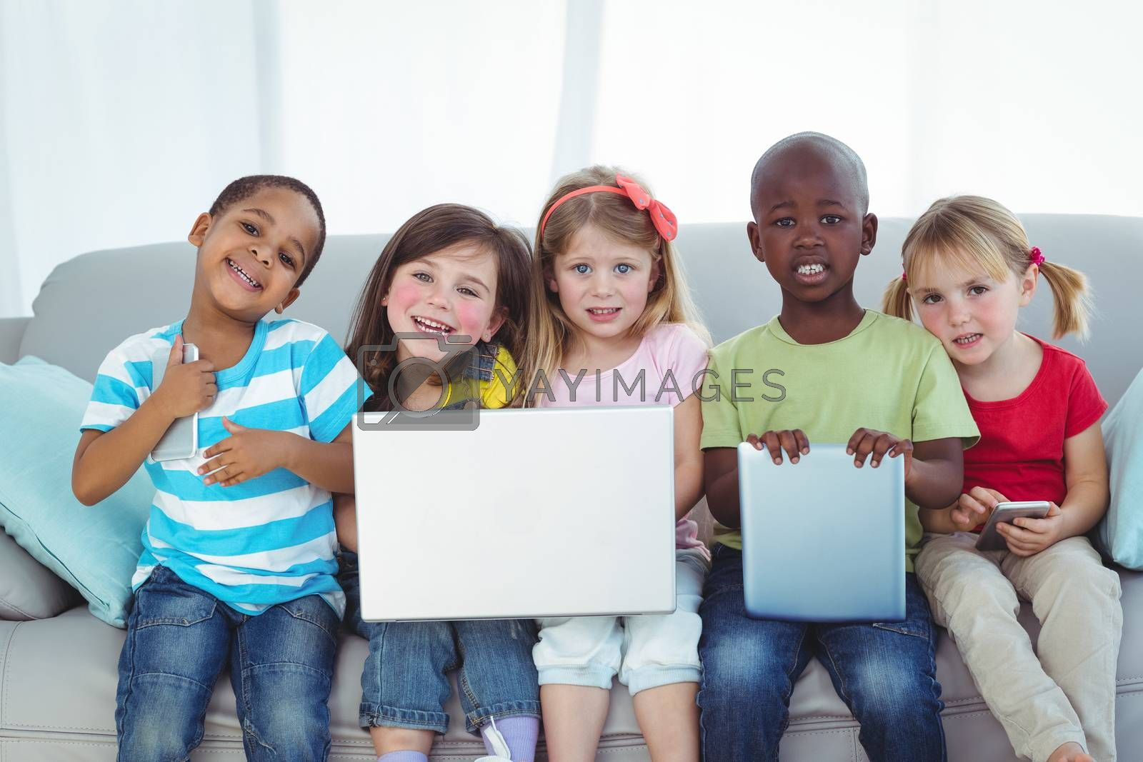 Happy kids using technology while sitting on the couch