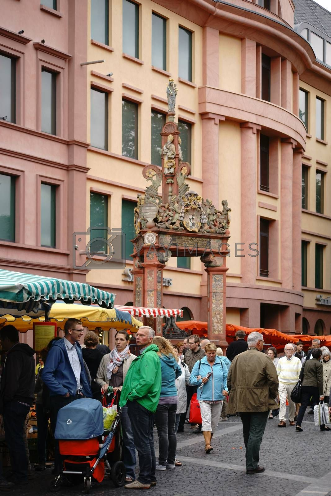 Mainz, Germany - September 04, 2015: The stalls of the weekly market in Mainz with visitors on the marketplace at the market fountain on September 04, 2015 in Mainz.
