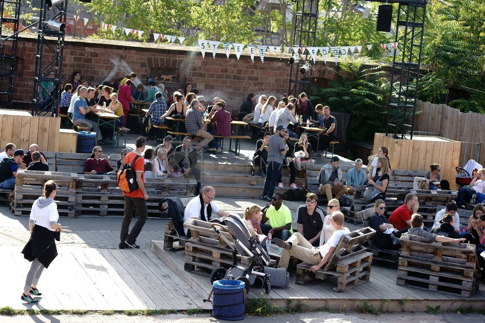 Mainz, Germany - October 02, 2015: Teenage viewers and visitors sit on wooden pallets and at beer tables at the Streefood Festival on October 02, 2015 in Mainz.