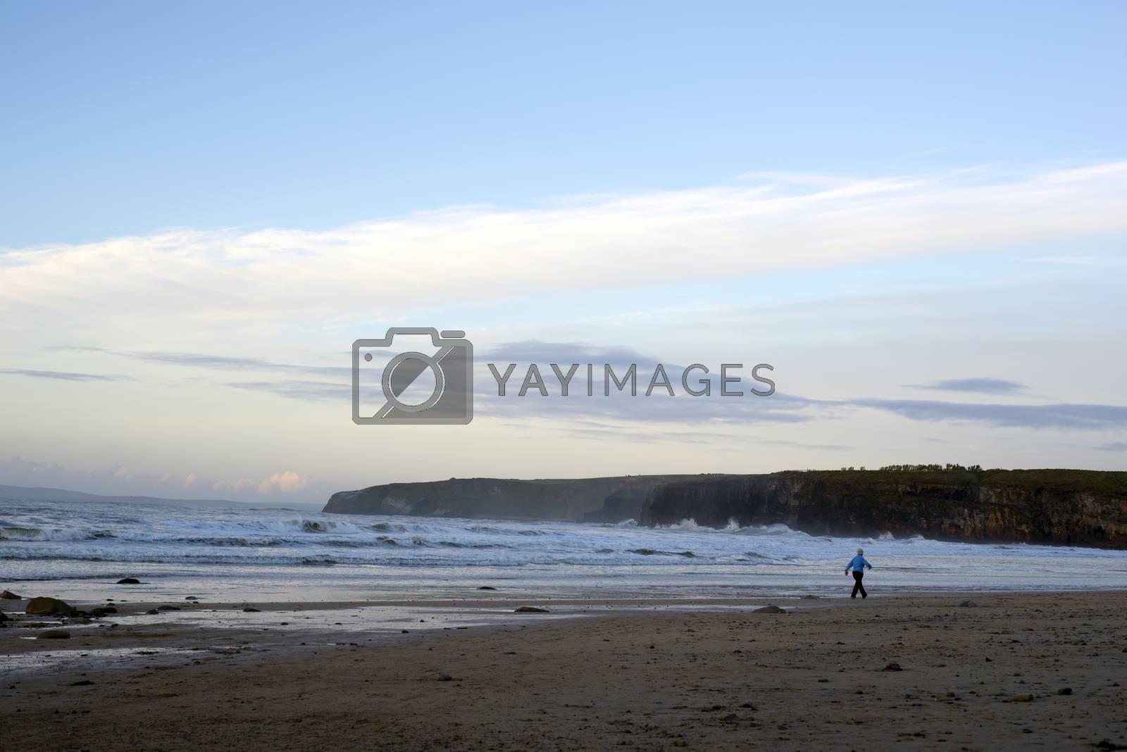woman walking at rocky beach near ballybunion on the wild atlantic way ireland on a cold day