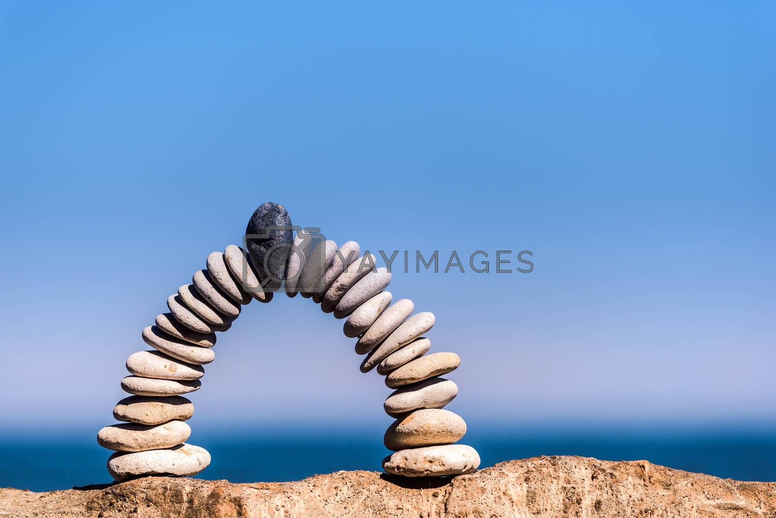 Black stone in the centre of arch of white pebbles