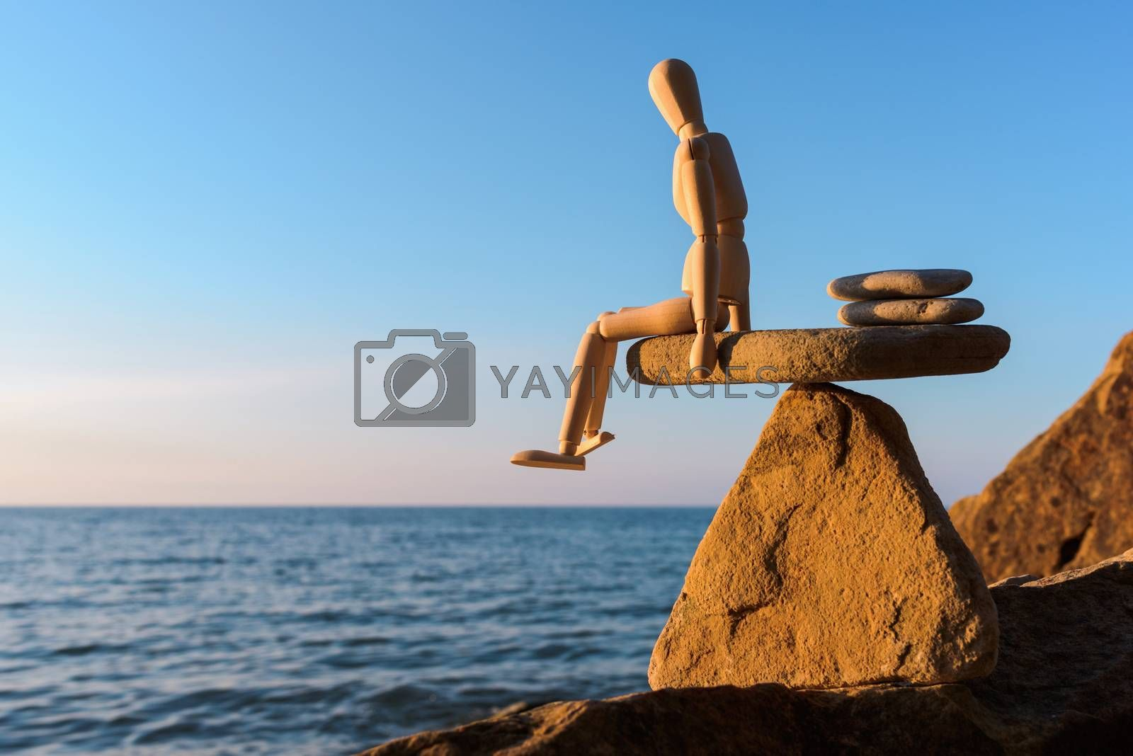 Wooden dummy sitting on the edge stone at the sea