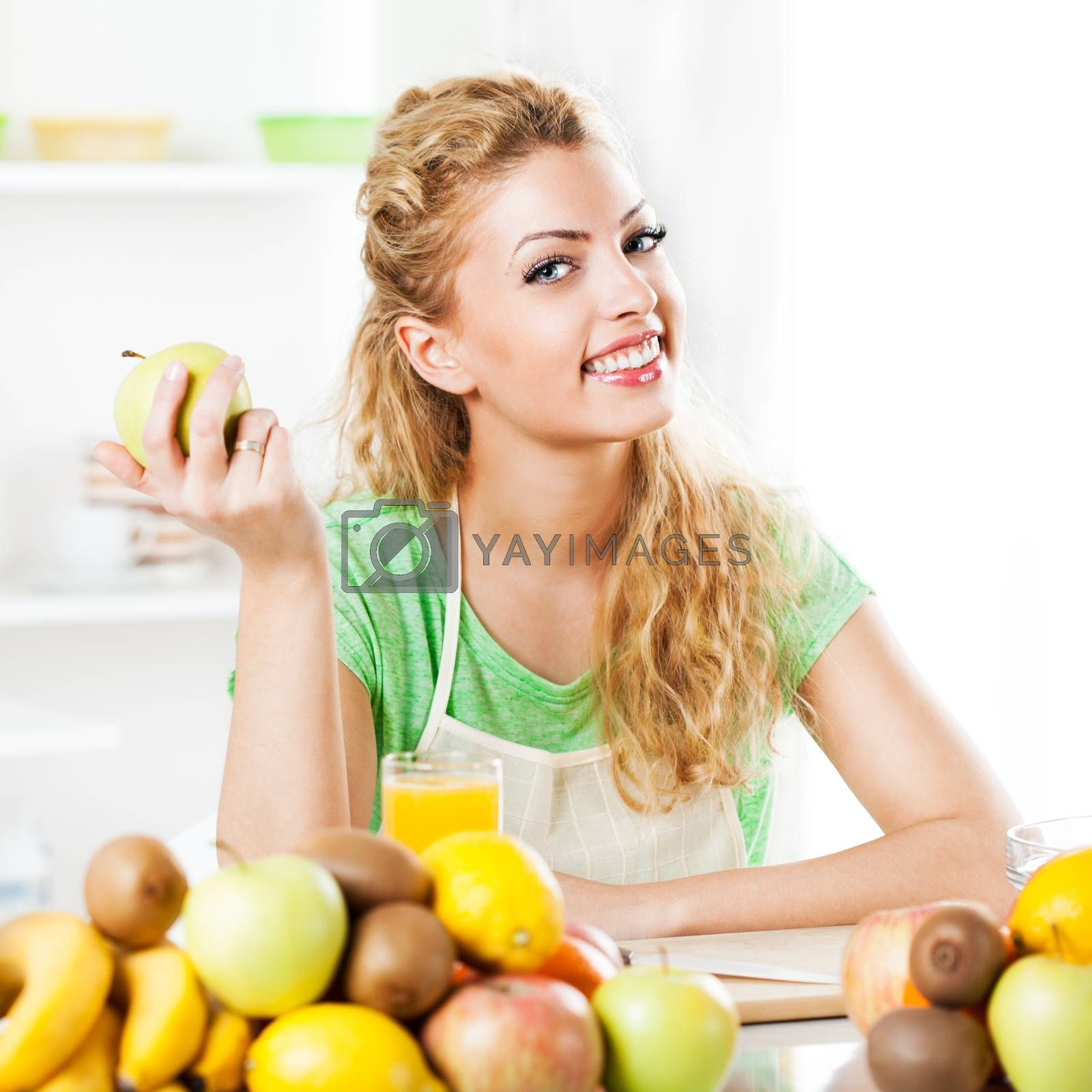 Beautiful young woman in the kitchen, holding an apple. Looking at camera.