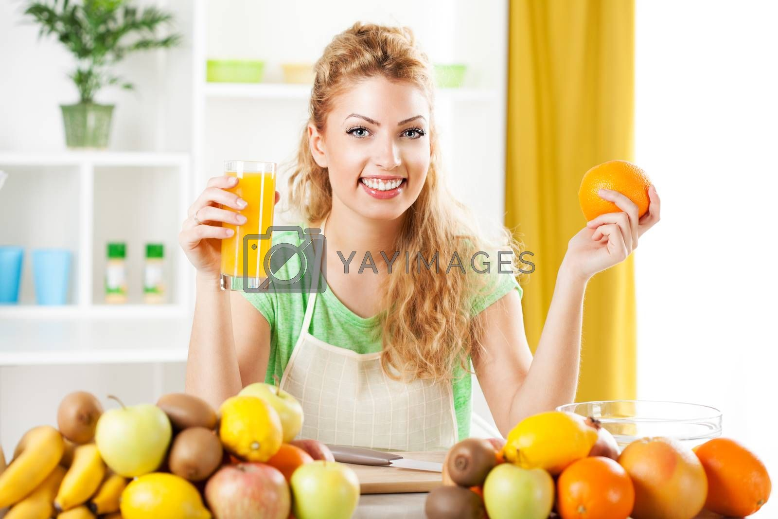 Beautiful young woman in the kitchen, holding orange and orange juice. Looking at camera.