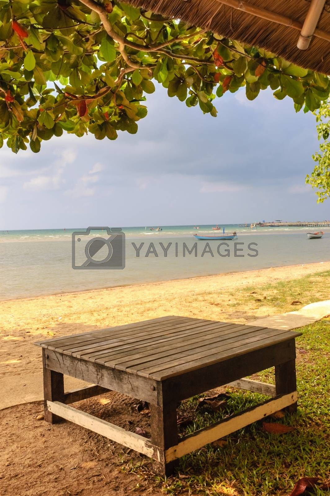 Relax on the beach wooden table in tree shade.