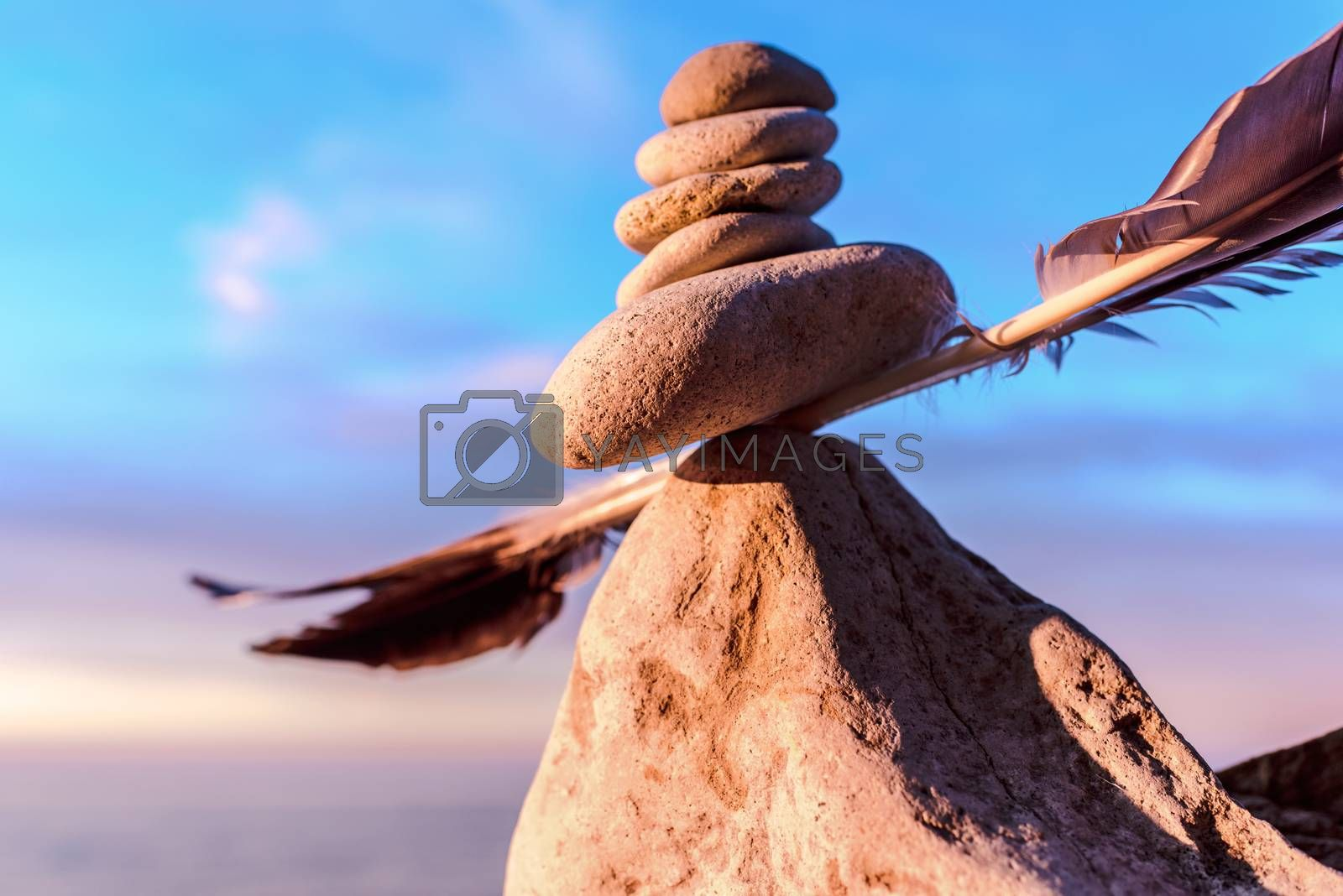 Balancing of stones and feather on the seashore