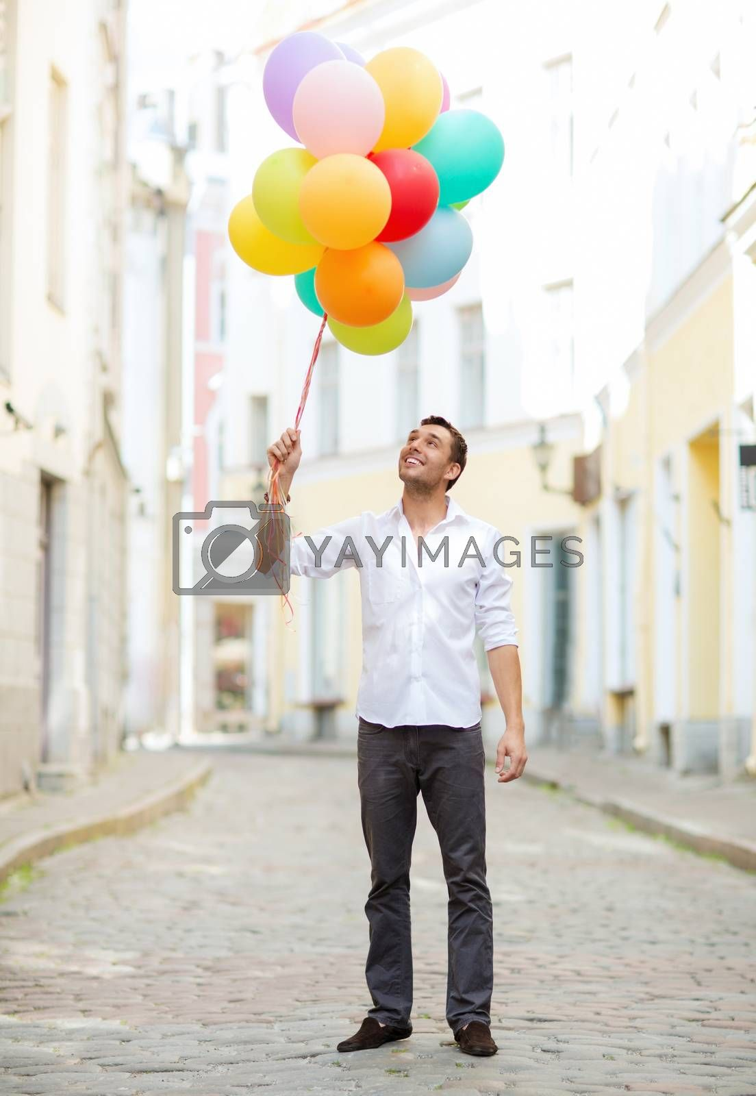 summer holidays, celebration and lifestyle concept - man with colorful balloons in the city