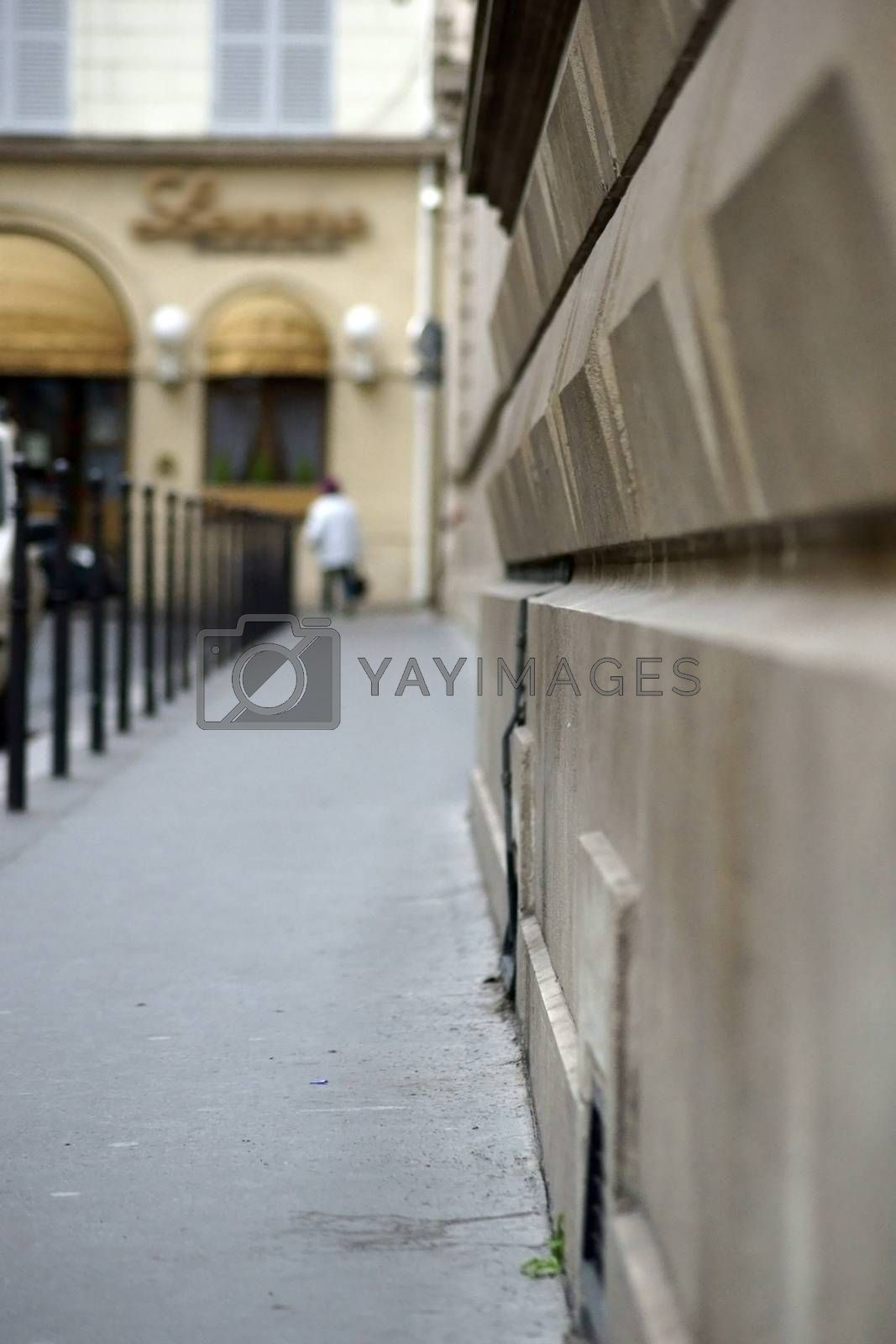 The blurred closeup of a walkway and a wall in Paris.
