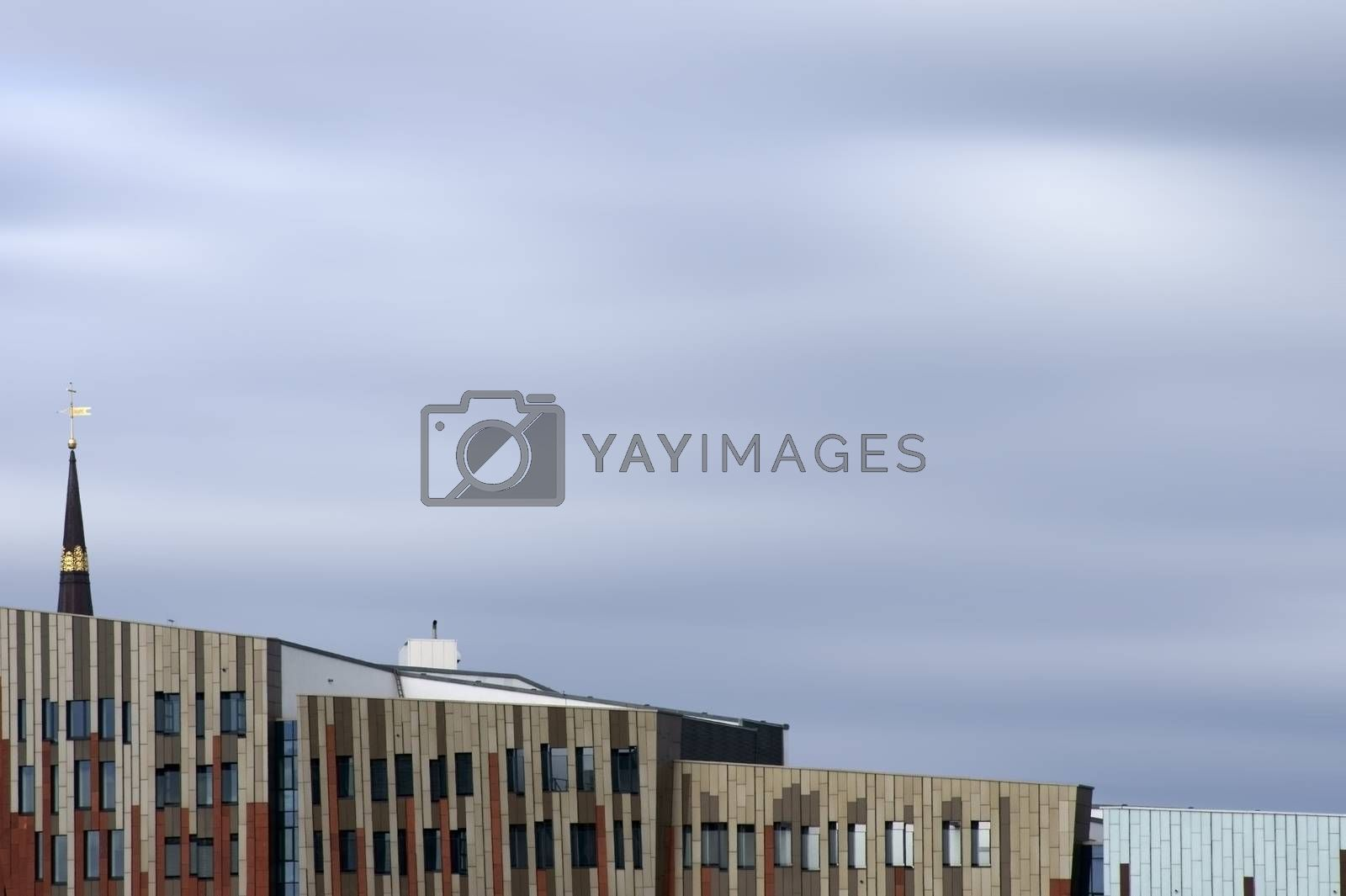 Hamburg, Germany - September 22, 2014: Modern and abstract architecture in the port of Hamburg with the spire of St. Catherine's Church above the roofs on September 22, 2014 in Hamburg.