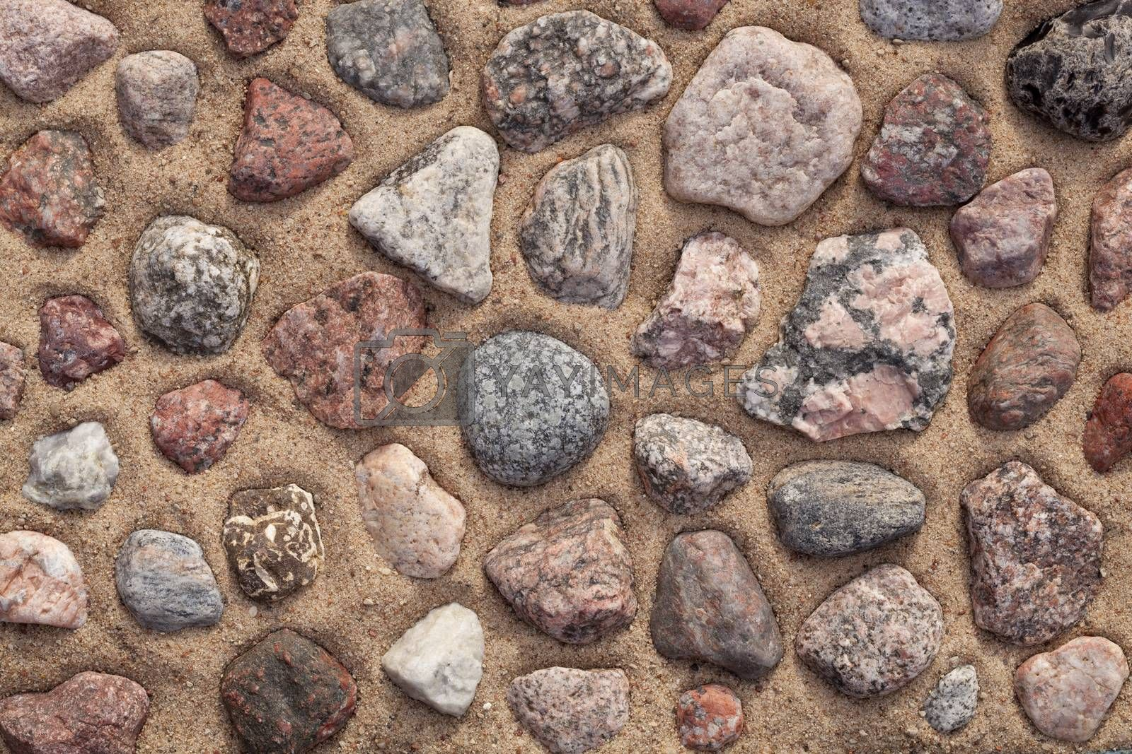 dry colourful stones arranged on sand as background