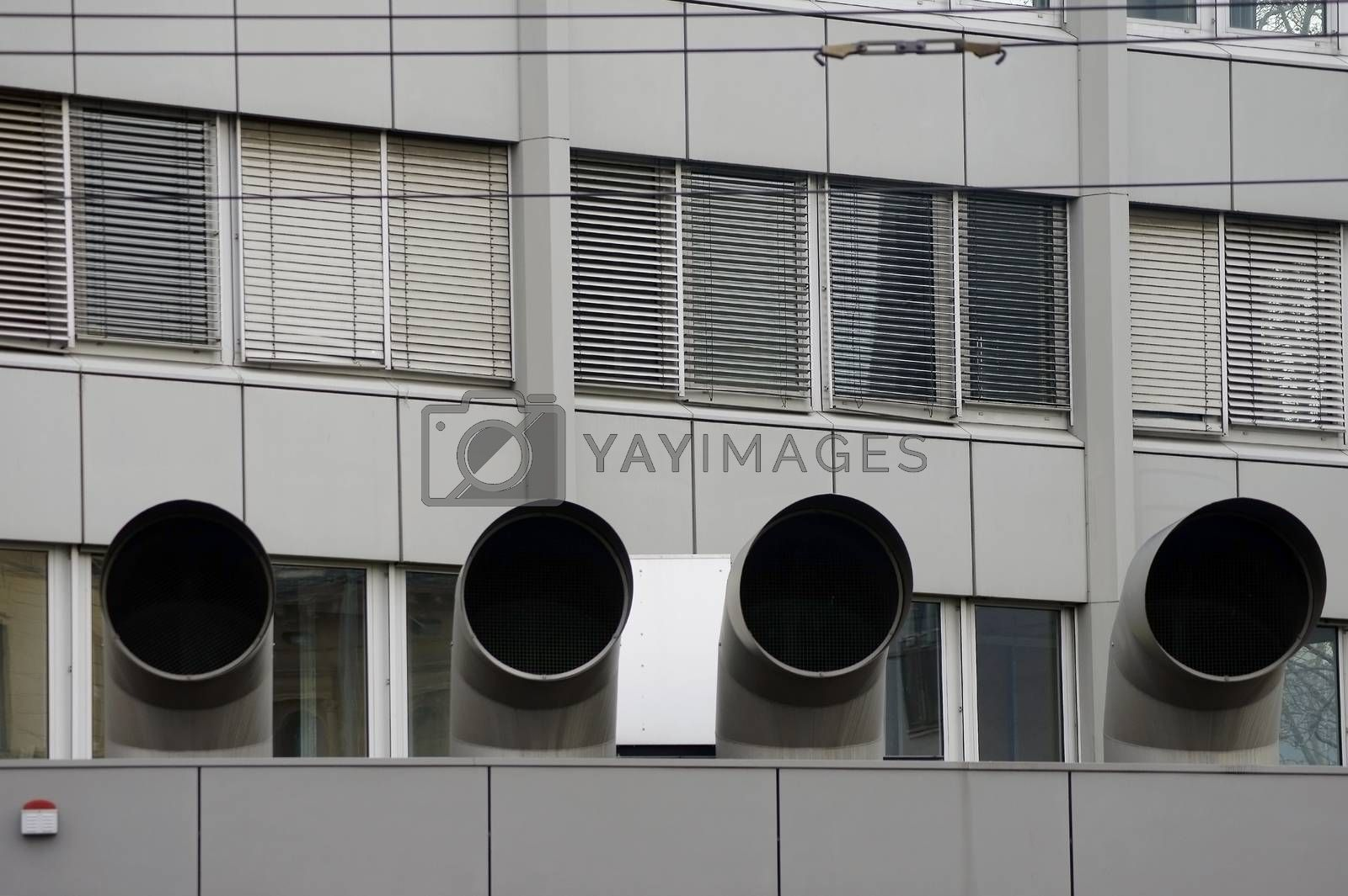 Four large ventilation pipes on a roof edge with an alarm system.