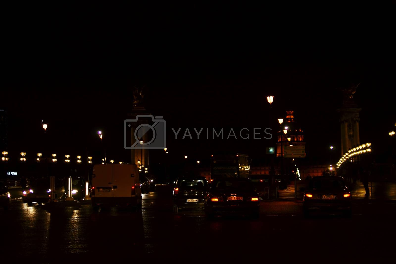 Paris, France - December 30, 2013: The illuminated Pont Alexandre III Bridge at night with traffic and the lighted Invalides dome  in the background on December 30, 2013 in Paris.