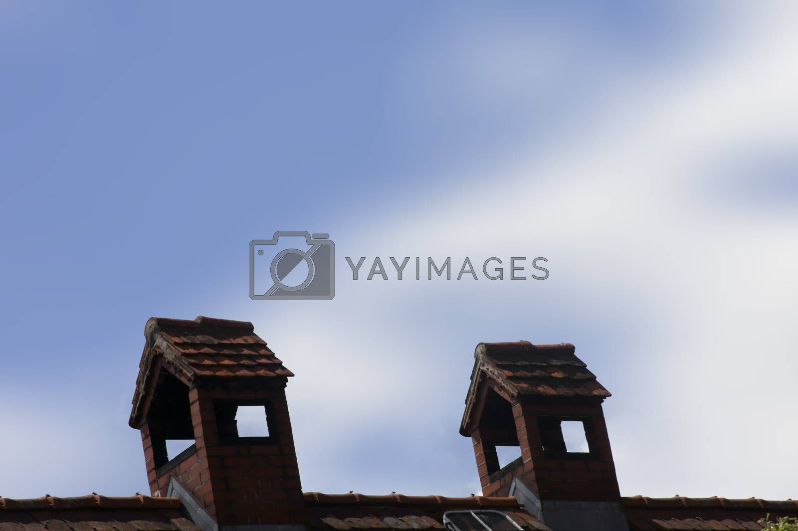 The close-up of a bizarre brick chimney on the roof of a house.