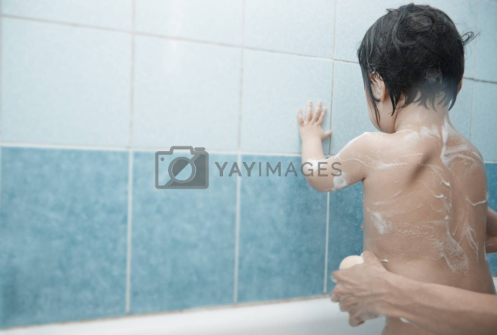 Mothers hands lathering child in the bath. Horizontal photo