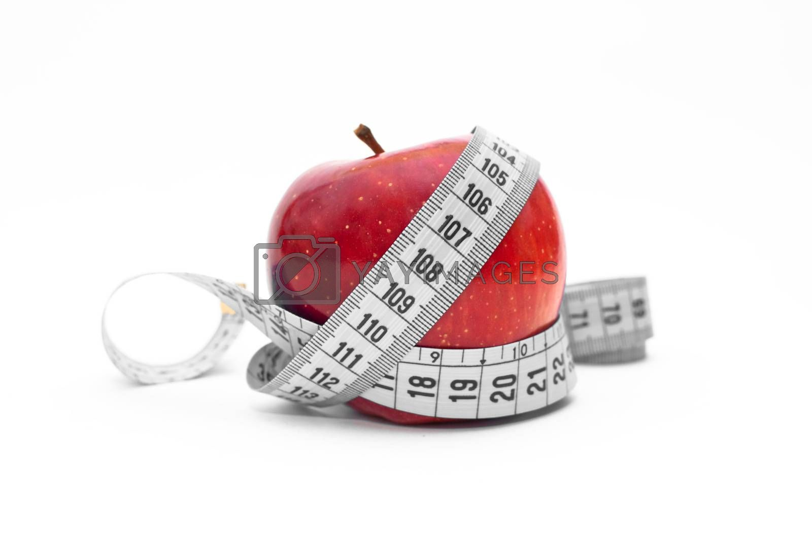 Organic apple and a tape measure over a white backround