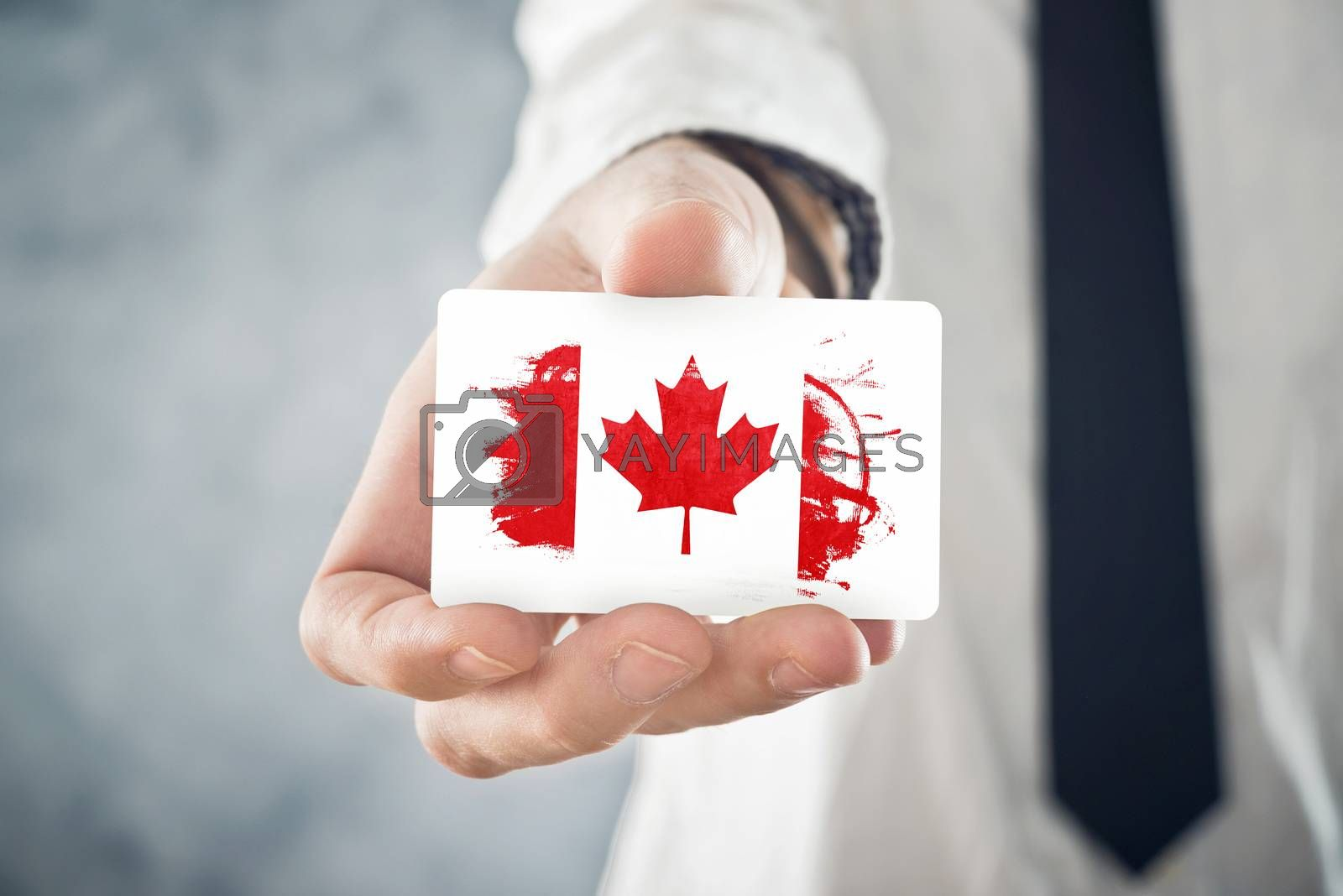 Canadian Businessman holding business card with Canada Flag. International cooperation, investments, business opportunites concept.