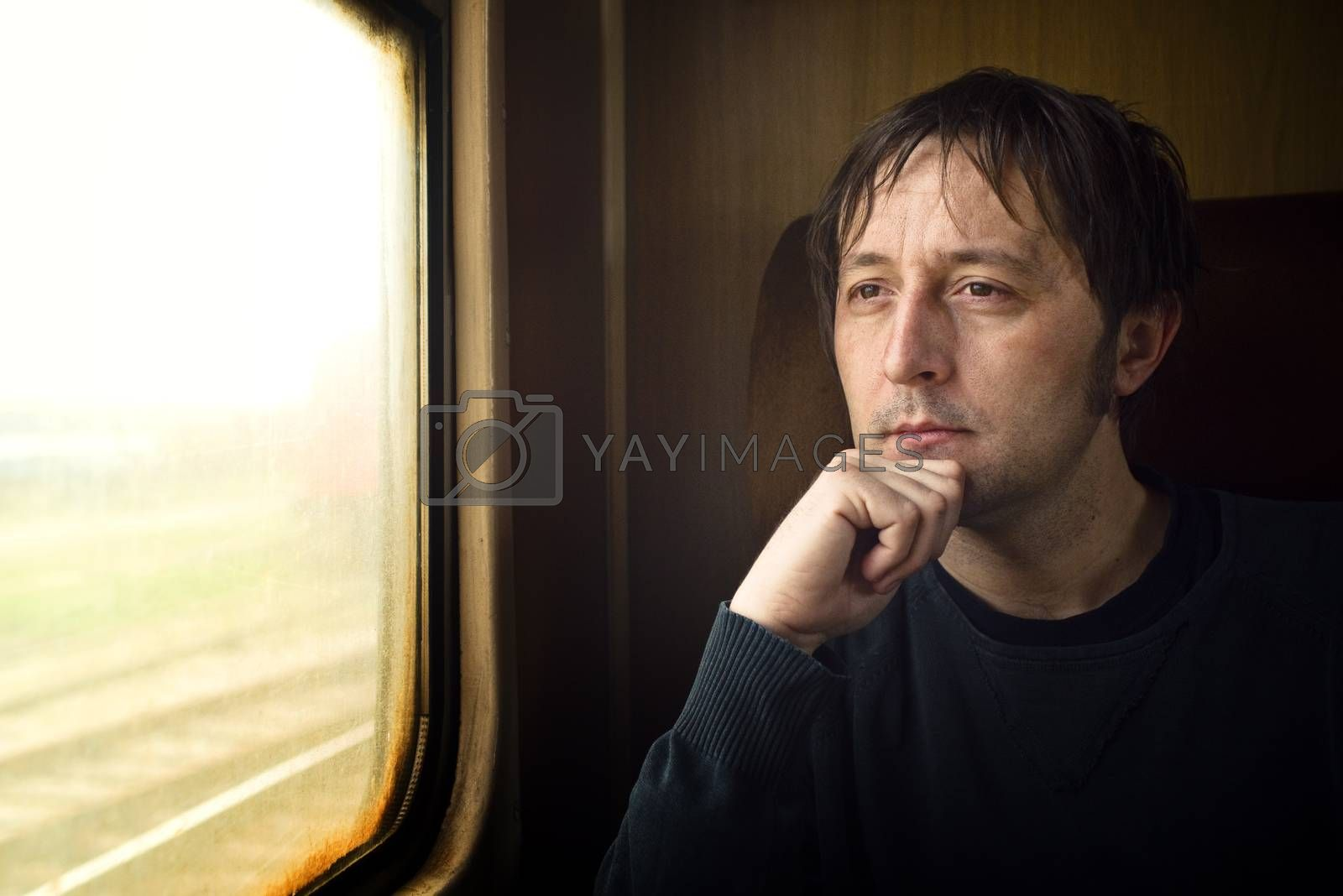 Traveling by train. Man traveling by train, looking through the dirty window.