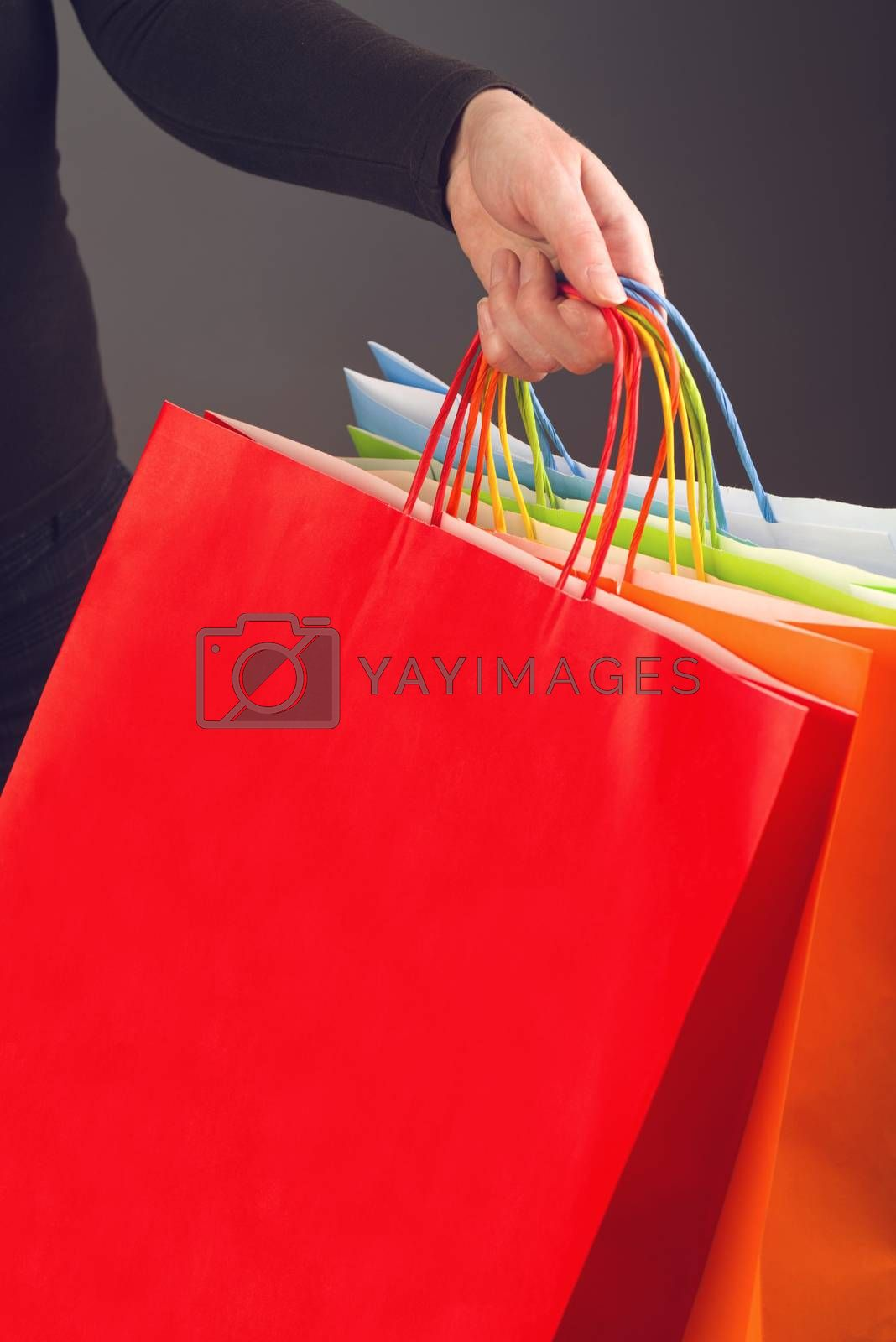 Woman holding colorful shopping bags for discount prices seasonal purchasing event. Saleout and clearance sale concept.
