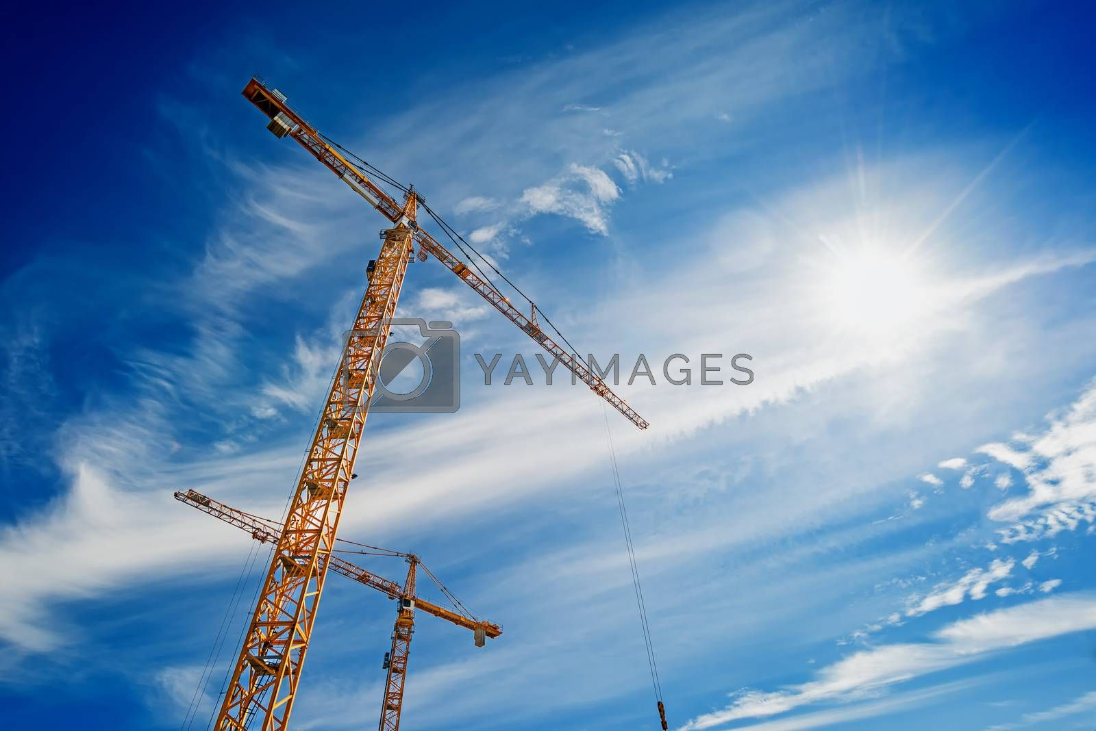 Two Yellow Industrial Cranes Working on Construction Site Against Blue Sky