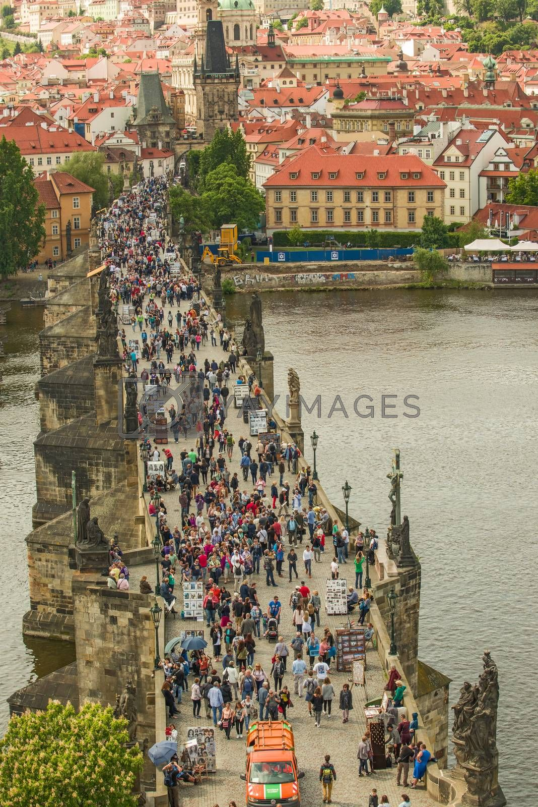 PRAGUE, CZECH REPUBLIC - MAY 22, 2015: Tourists Crossing Charles Bridge, Famous Attraction in Czech Republic Capital. Prague was visited by more than 8 million people in 2014.