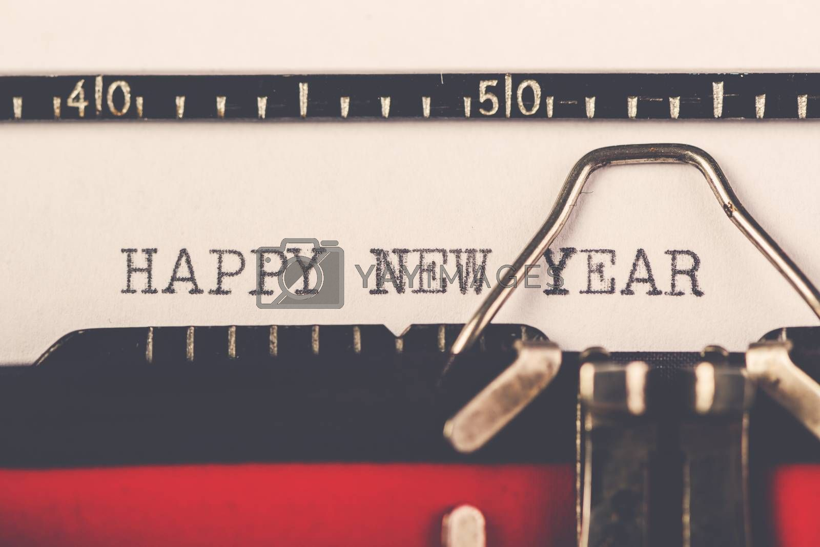 Happy New Year on old typewriter machine, hipster lifestyle holiday letter and greeting card, retro toned, selective focus