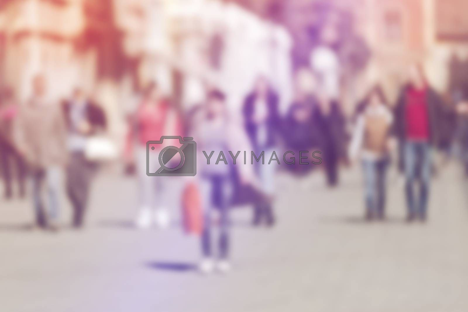 Crowd of People Walking On the Street in Bokeh, unrecognizable group of men and women with shoppingbags as blur urban background