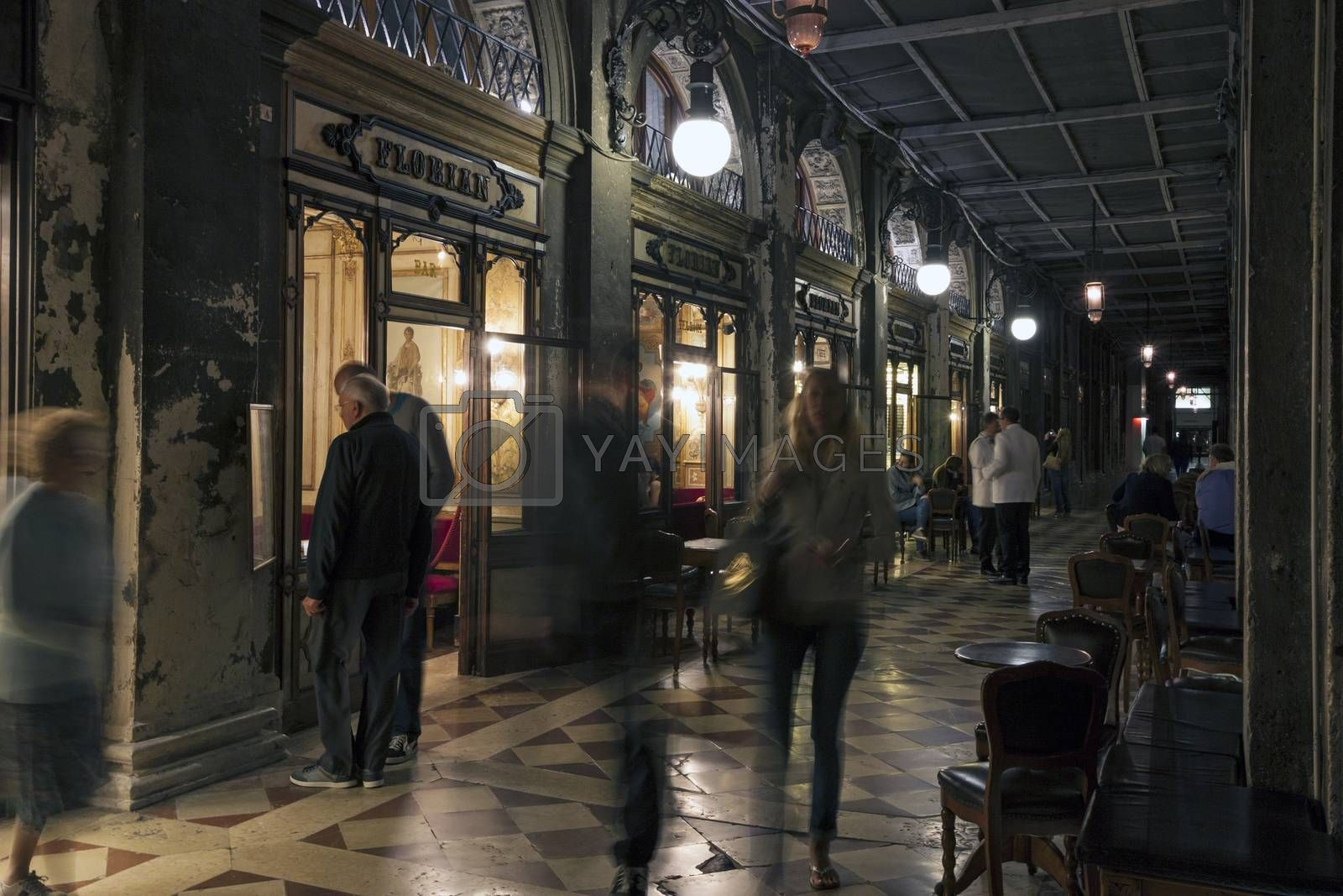 VENICE, ITALY - MAY 29, 2015: The oldest coffee house Florian in Piazza San Marco in Venice at night. Tourists wandering around, some of them in motion blur, some exploring cafe menu.