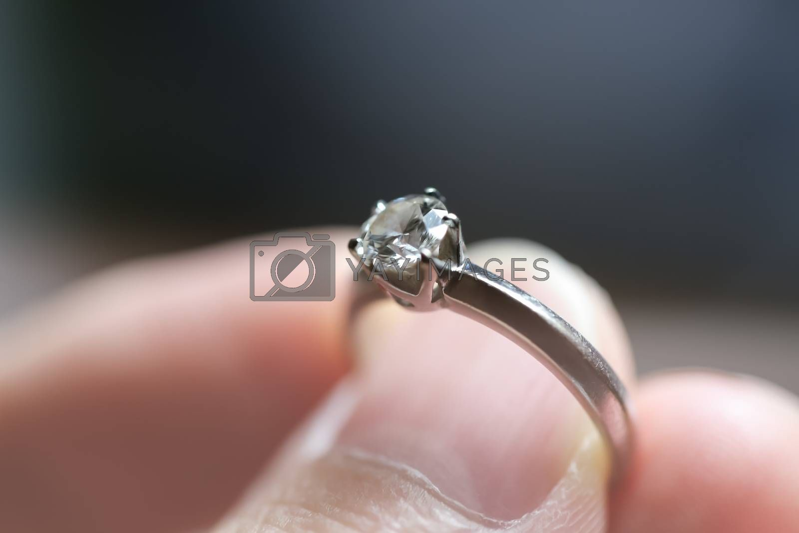 Diamond ring was holding by thumb and finger