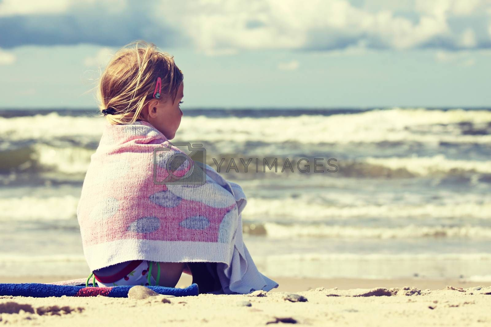 Lonelly little girl sitting on the beach covered with towel and looking at the sea
