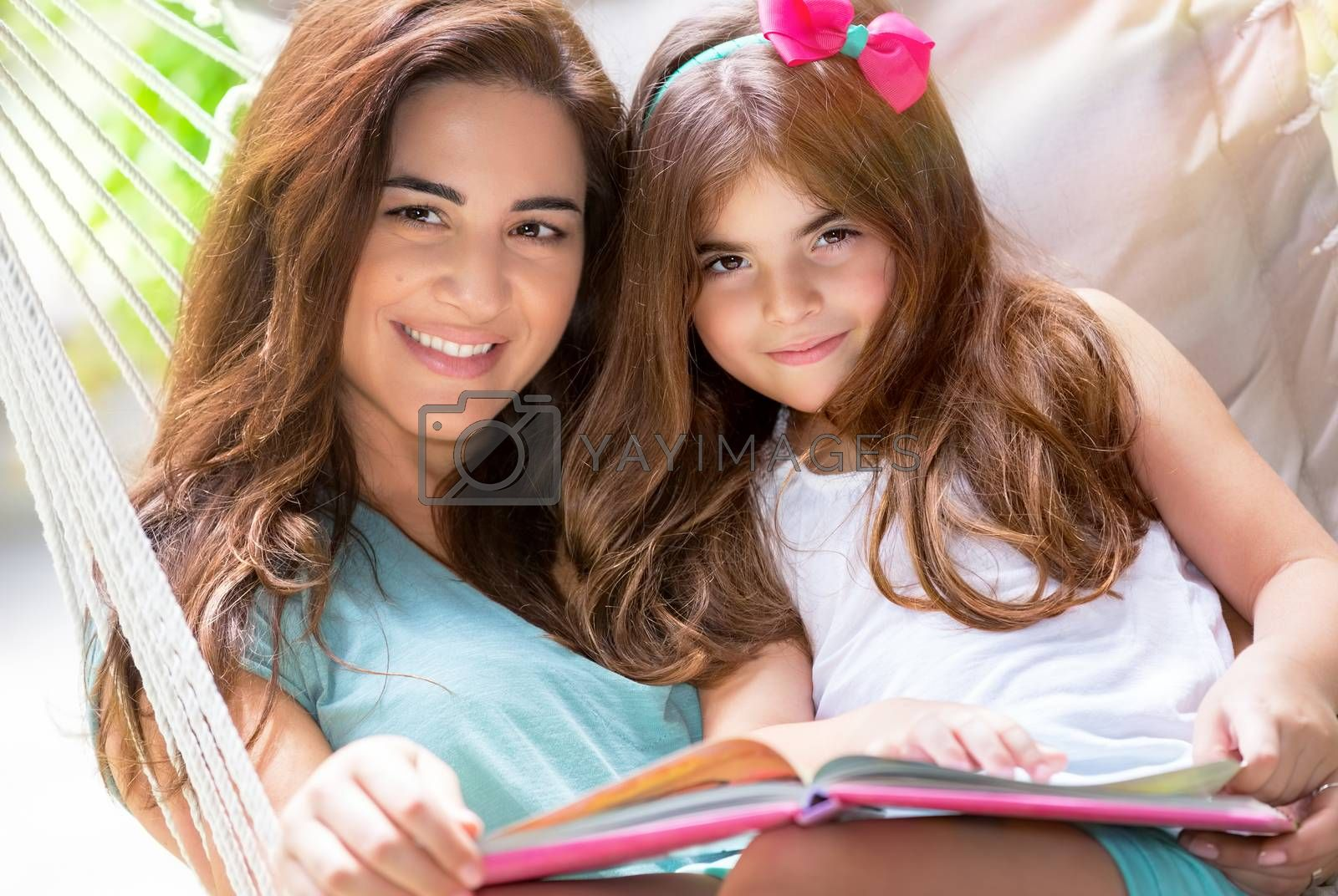 Portrait of beautiful happy mother with cute little daughter sitting on backyard in hammock and reading interesting book, nice lovely family
