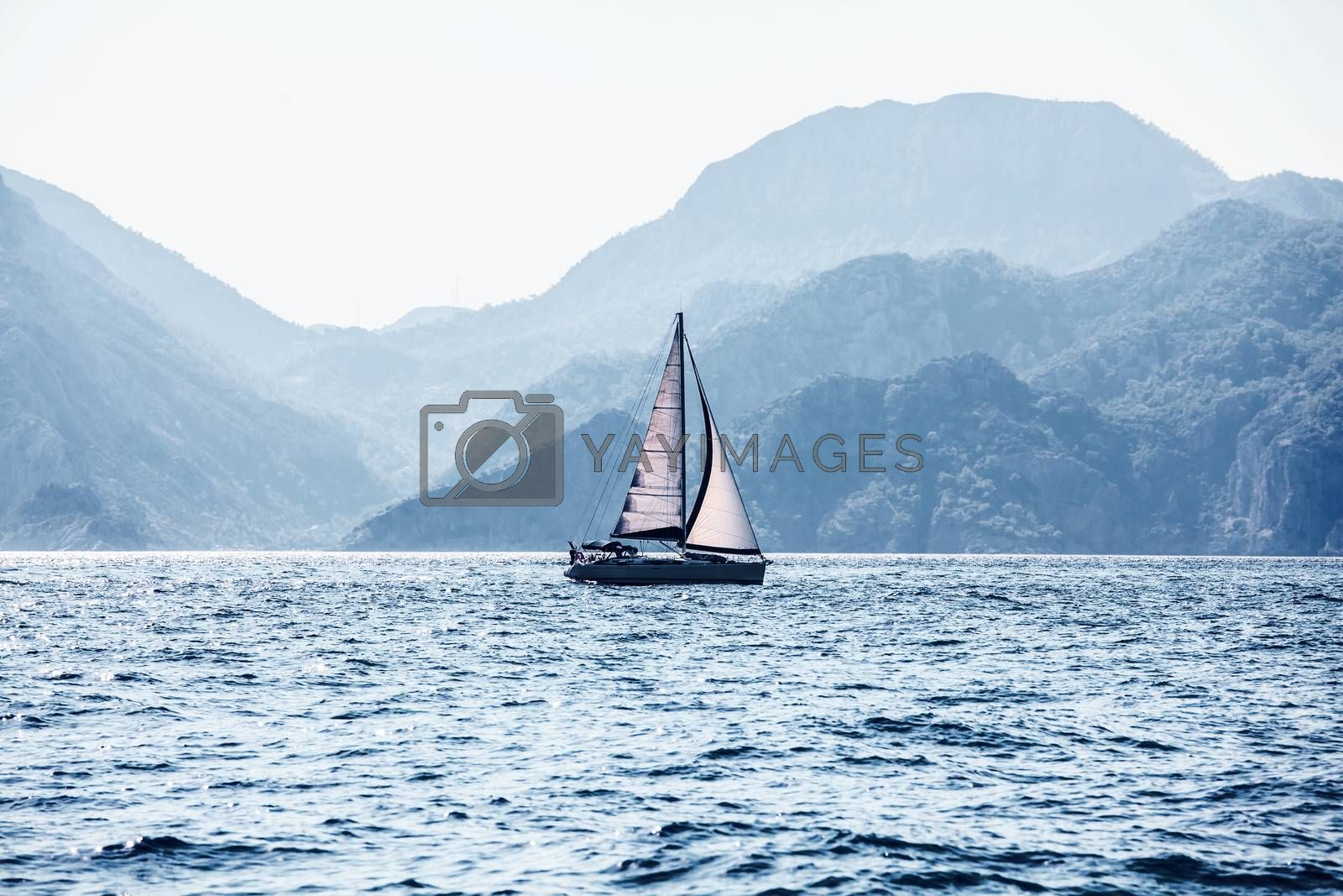 Beautiful sea landscape, sailboat sailing on the distance on great majestic mountains background, romantic cruise in the Mediterranean sea, beauty of Turkish nature