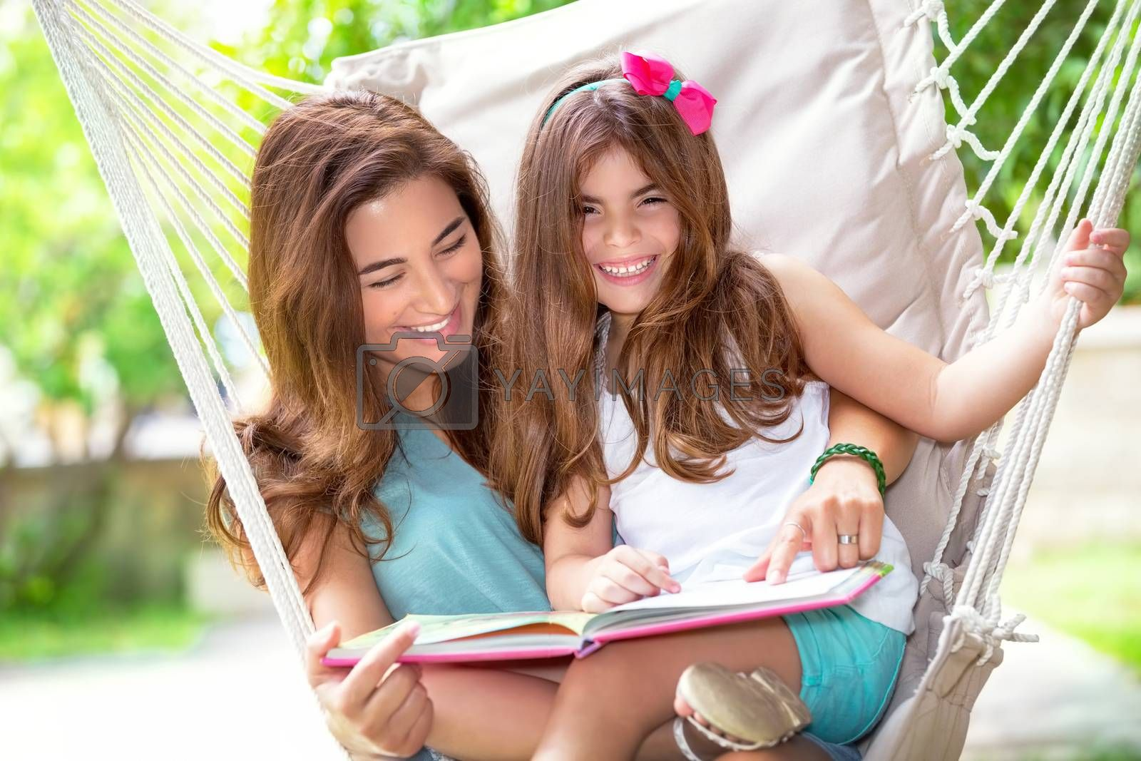 Portrait of beautiful happy mother with cute little daughter sitting on backyard in hammock and reading funny story, nice lovely family