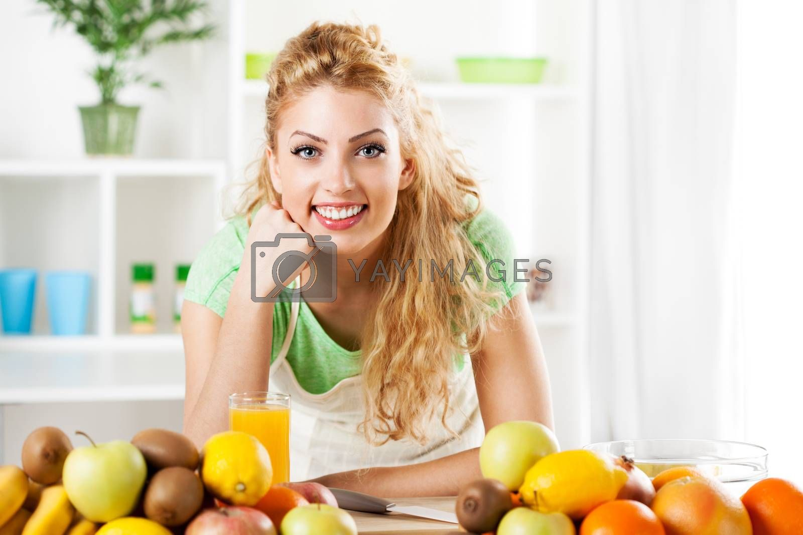 Beautiful young woman in the kitchen with fruits. Looking at camera.