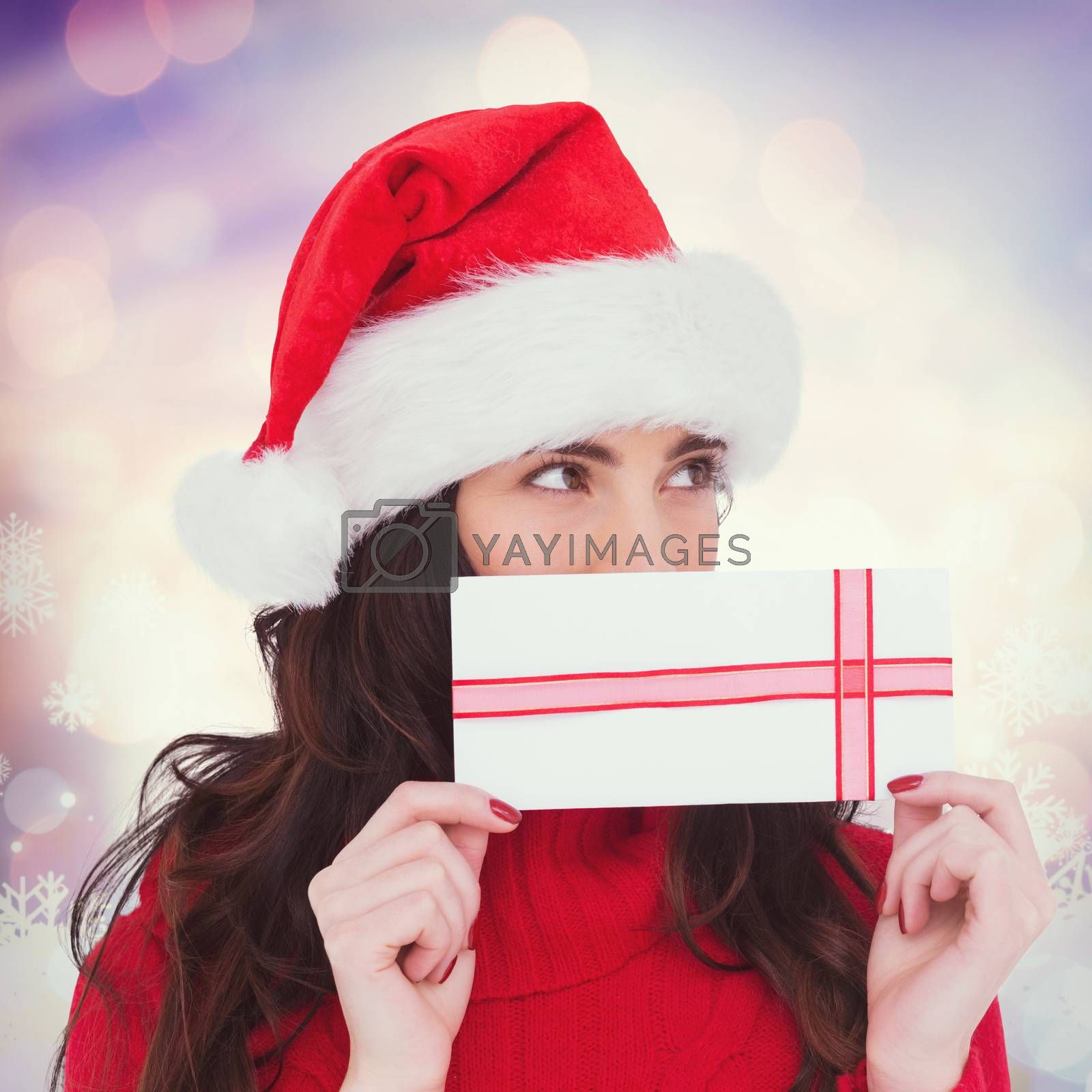 Composite image of festive brunette holding a gift by Wavebreakmedia