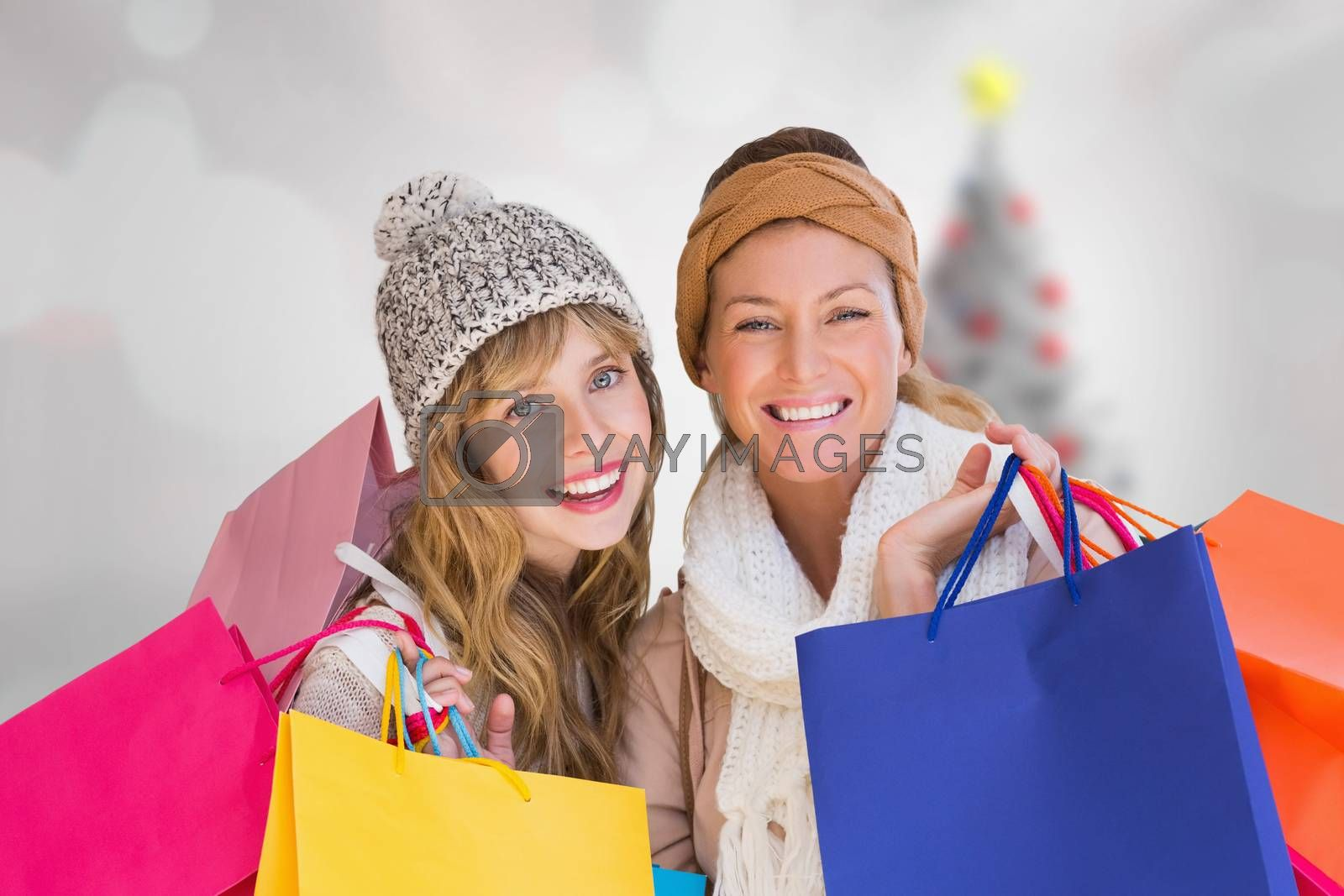 Beautiful women holding shopping bags looking at camera  against blurry christmas tree in room