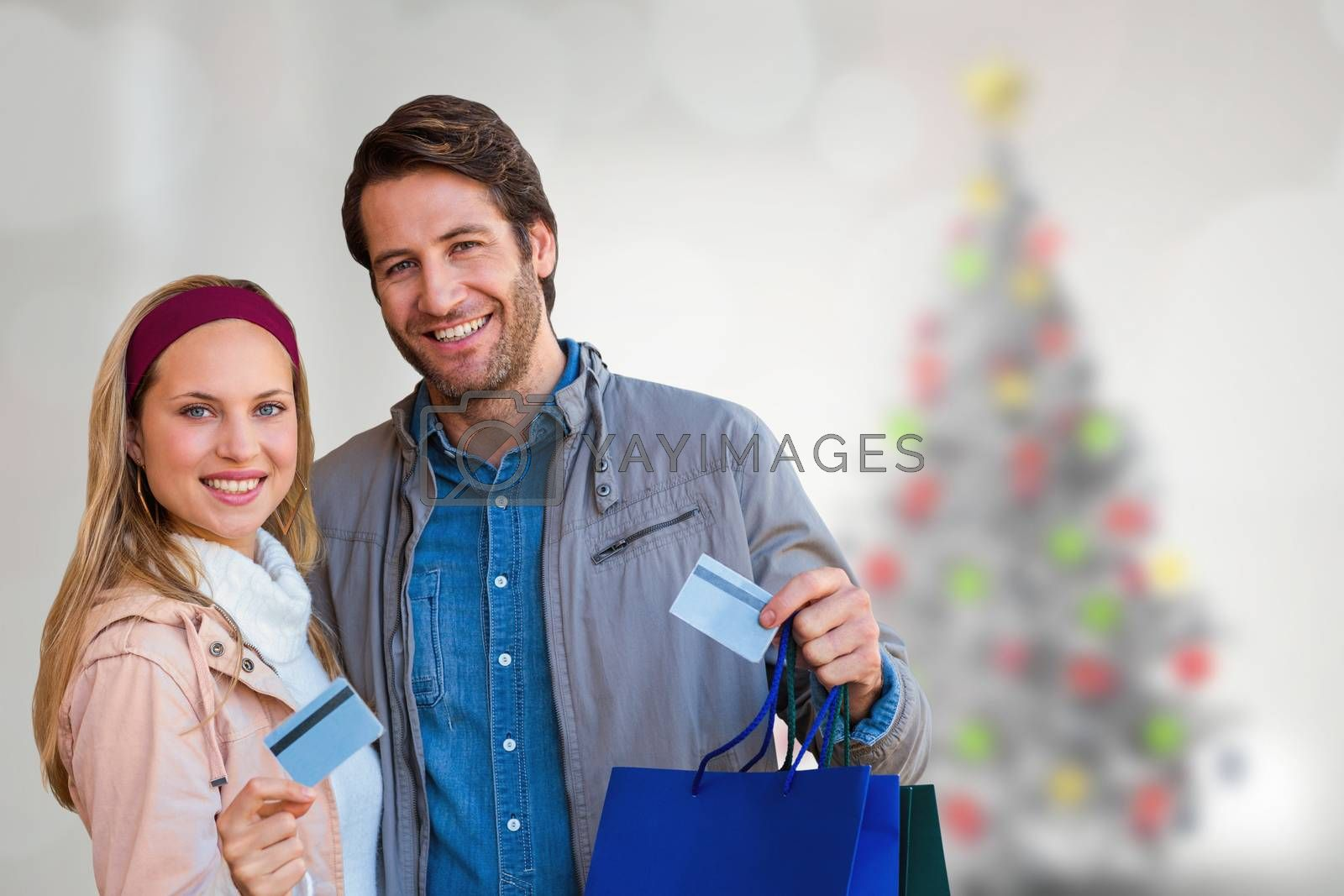 Smiling couple with shopping bags showing credit card against blurry christmas tree in room