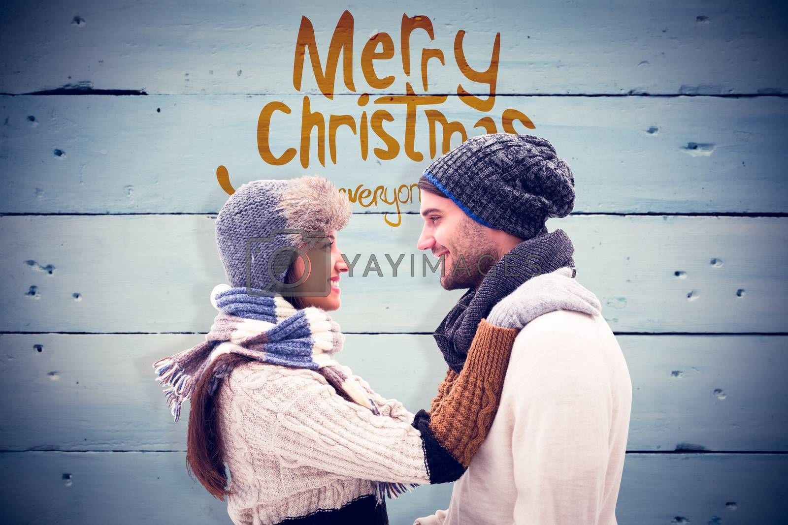 Young winter couple against painted blue wooden planks