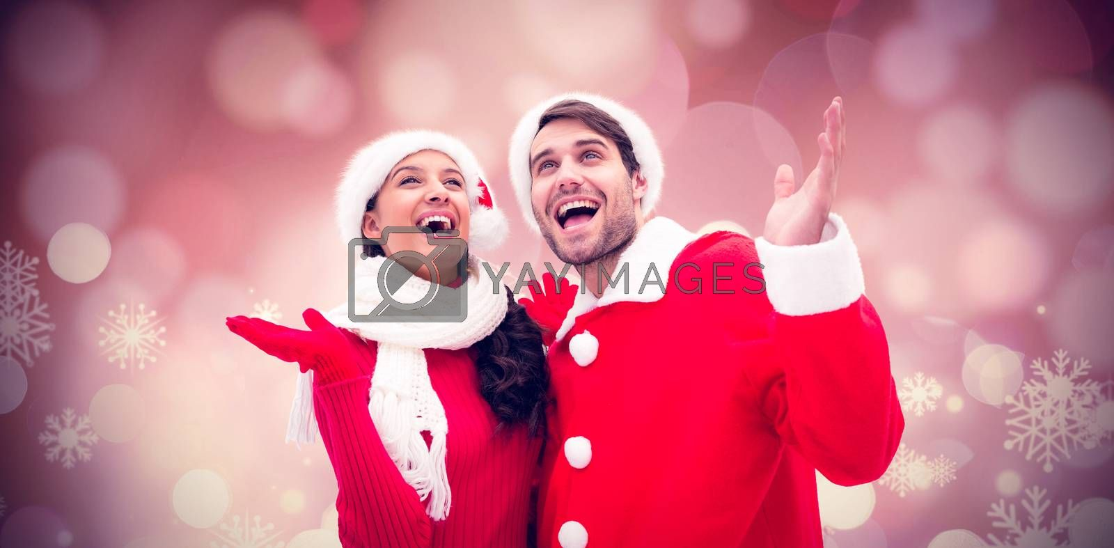 Festive young couple against glowing christmas background