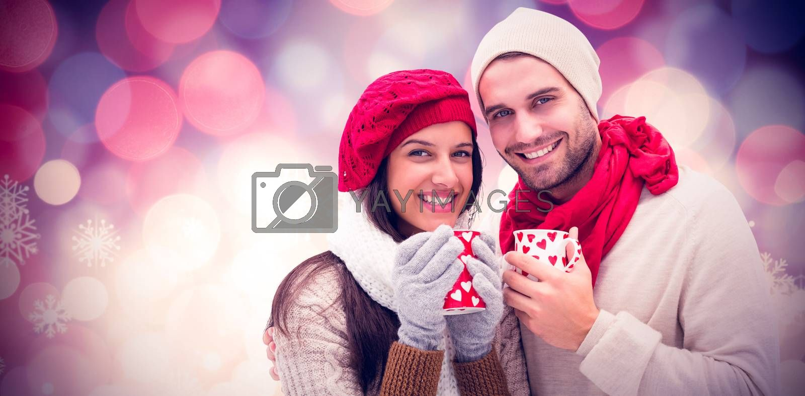 Winter couple holding mugs against glowing christmas background